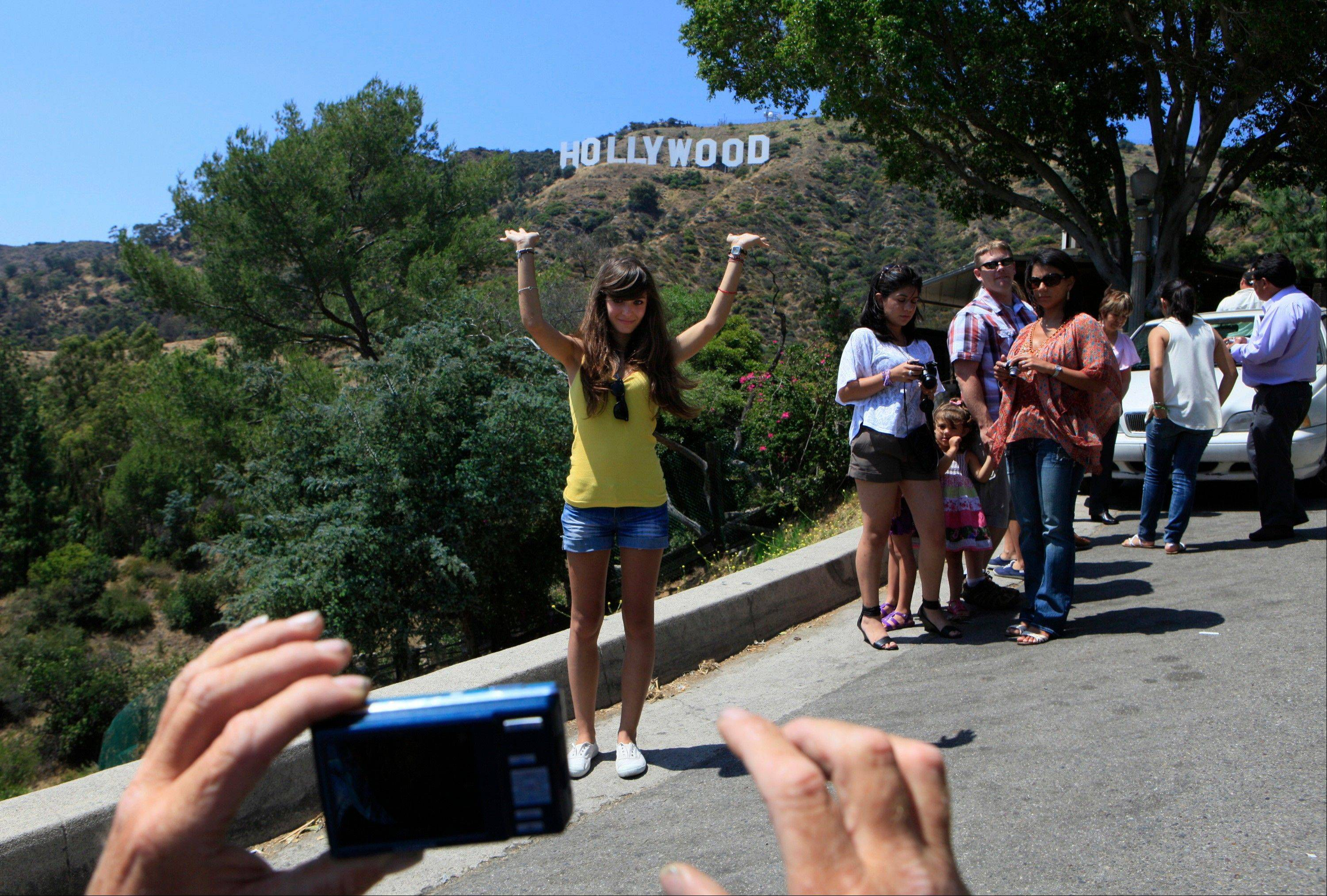 Tourists photograph each other on a hill with a view of the Hollywood sign in Los Angeles.