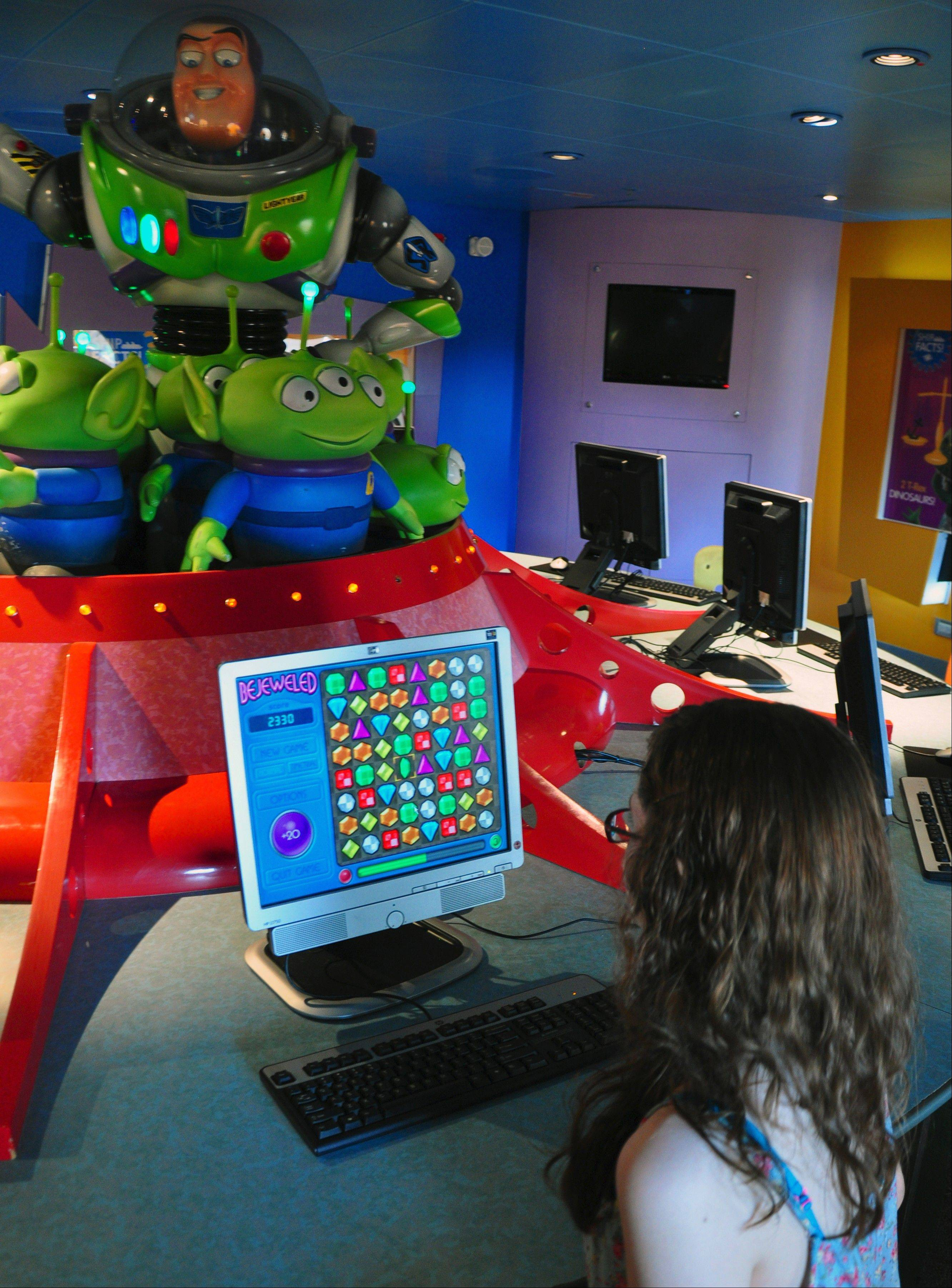 Kaily Vogel of Roselle checks out the video games in the Oceaneer Lab, one of several children's areas on the Disney Wonder.