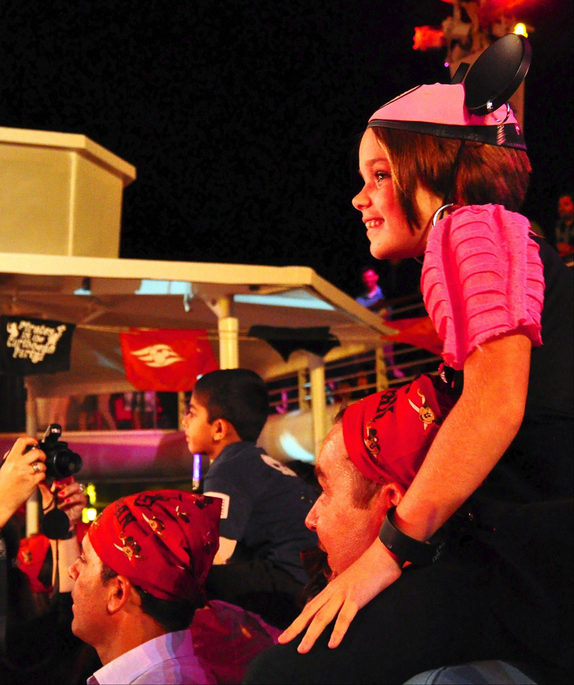 Kids perch on parents' shoulders to see the action during the Pirates IN the Caribbean deck party.