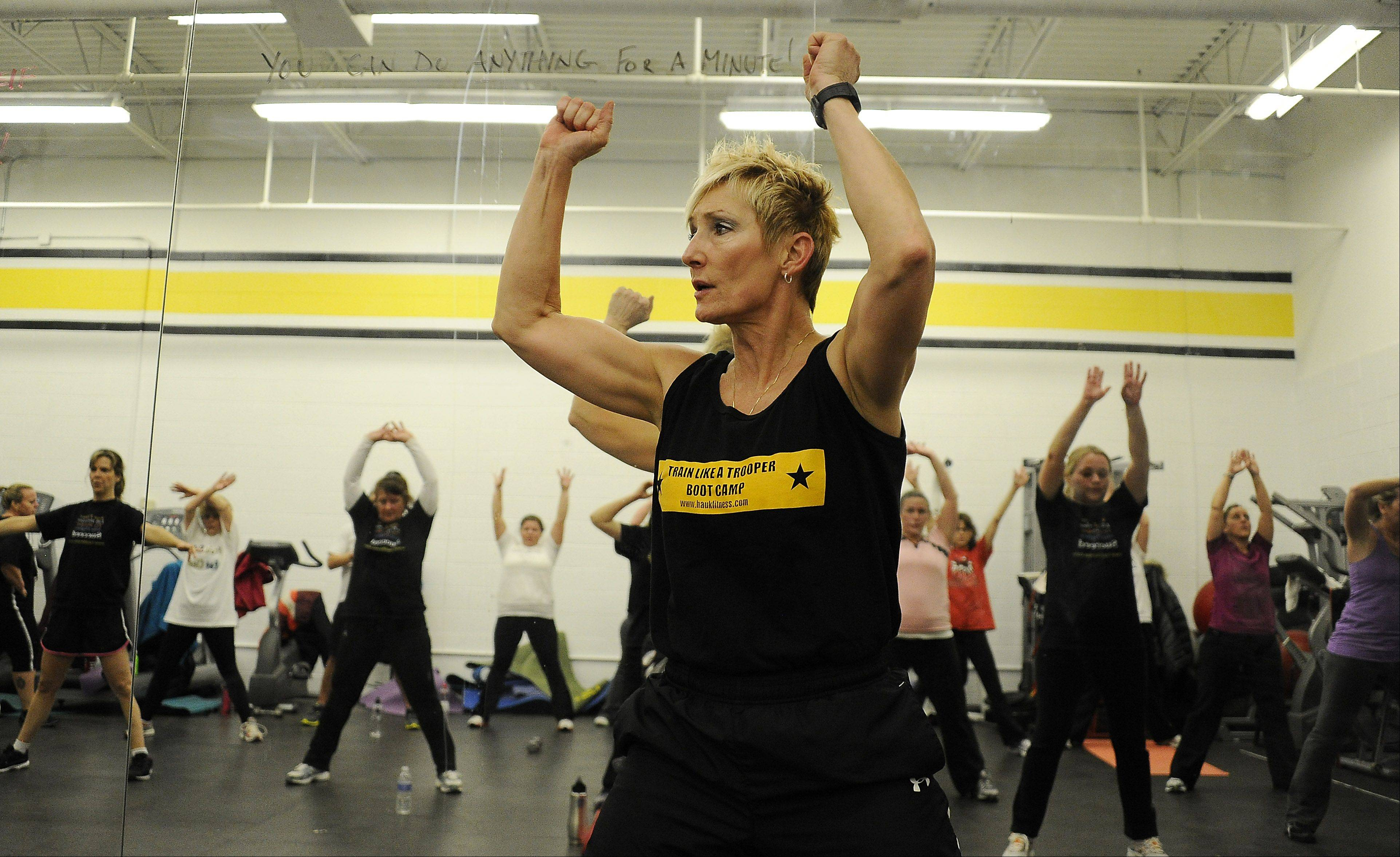 Retired Illinois State Police captain Tami Haukedahl leads her Train Like a Trooper Boot Camp class of suburban moms and dads though their paces.