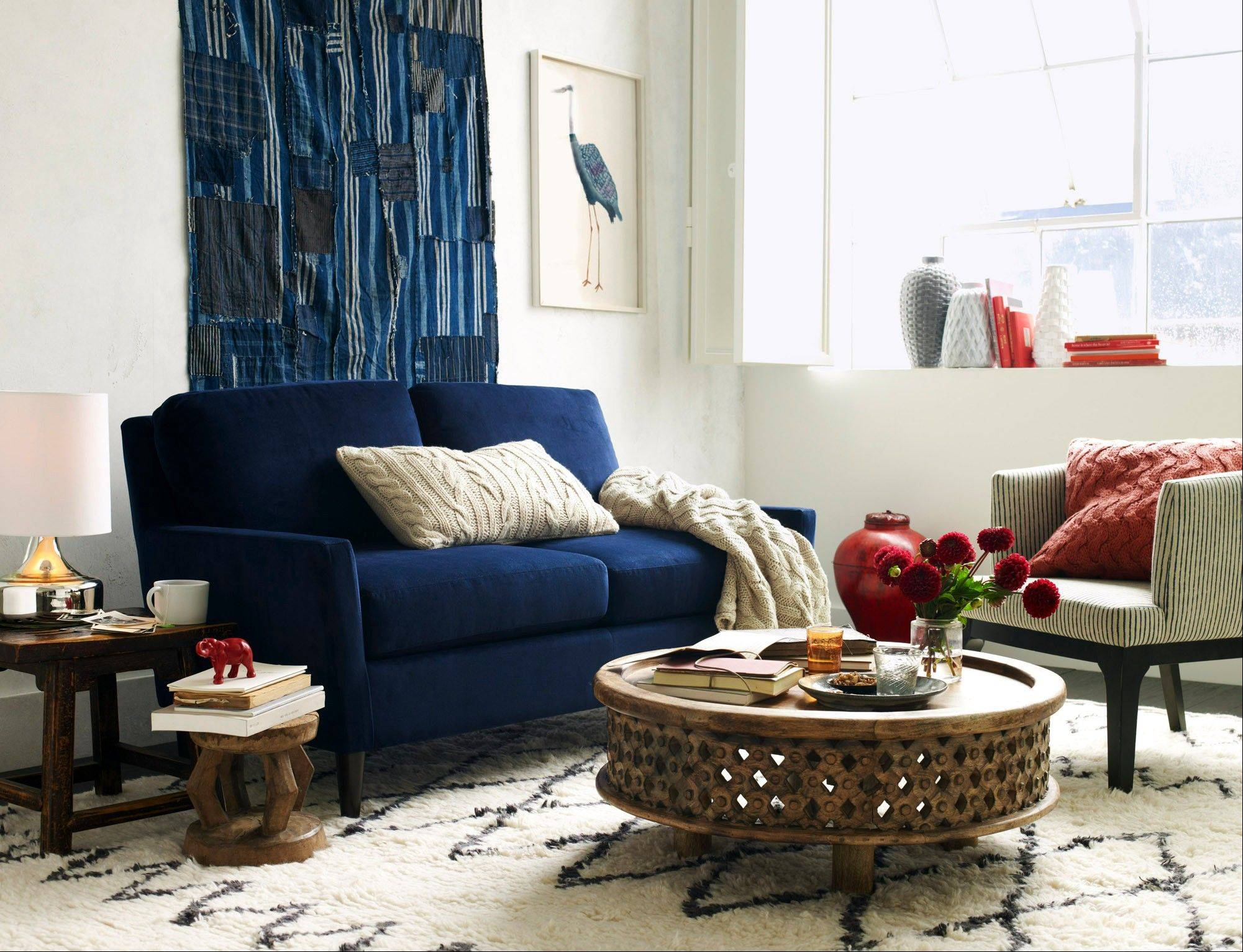 "This room is anchored by West Elm's indigo Everett loveseat, upholstered in a velvet they call ""ink blue""; indigo interiors go with almost everything."