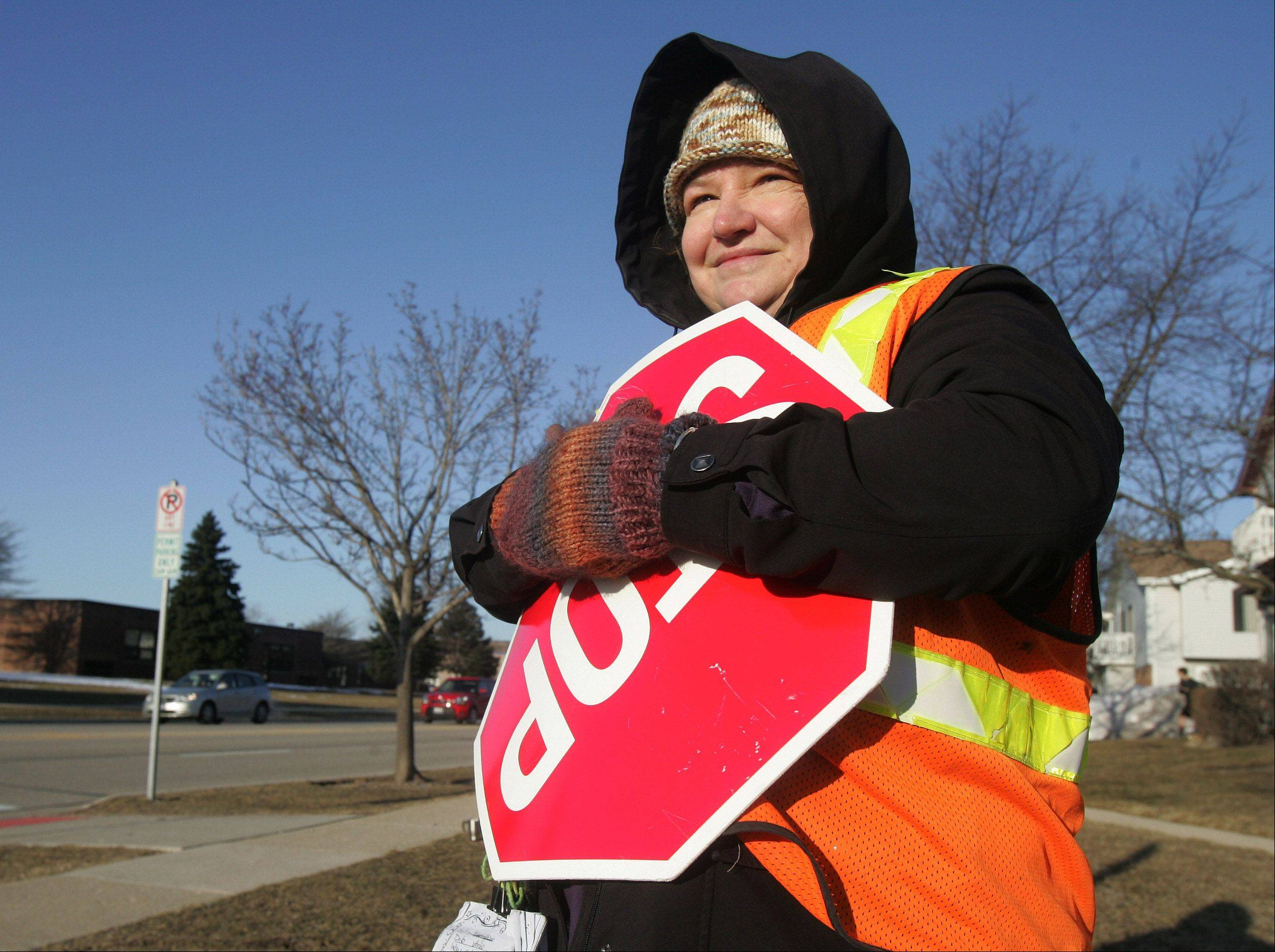 On the first day of Spring, crossing guard Sally Speer, of Mundelein, tries to keep warm as she stands in the frigid weather outside Hawthorn Elementary School in Vernon Hills Wednesday.