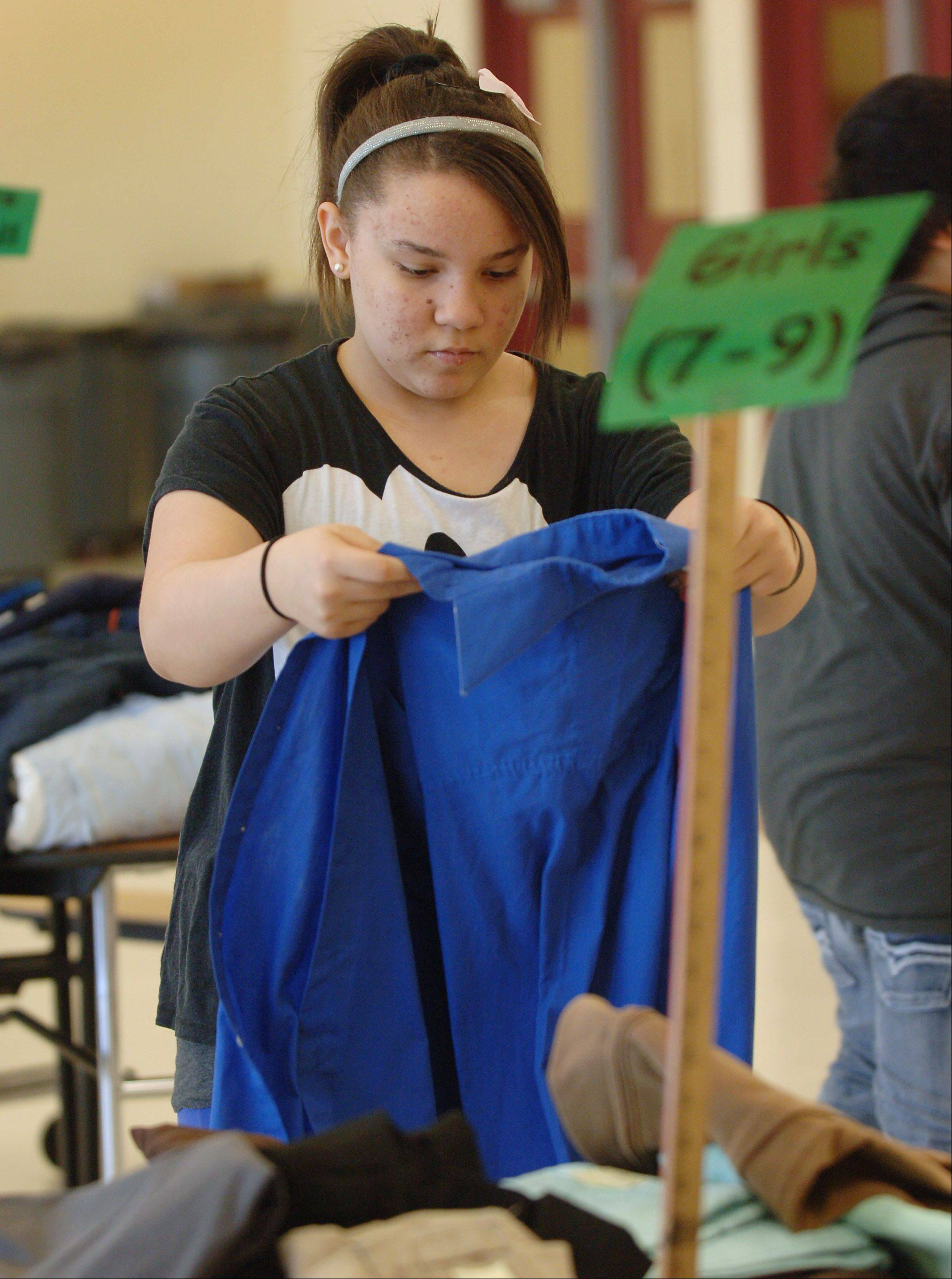 The John T. Magee Middle School BIONIC (Believe It or Not I Care) group held a free clothing give-a-way during the school's parent-teacher conferences on Thursday in Round Lake. BIONIC sixth grade member Symone Henderson folds clothes during the event.