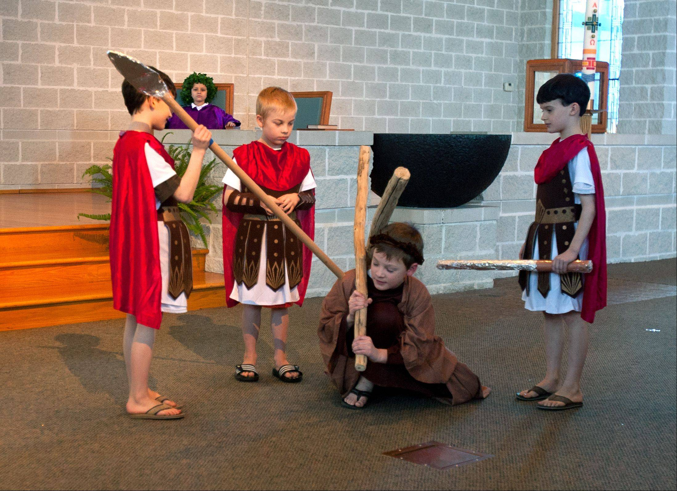 Jesus, portrayed by Jack Zgutowicz, falls down during a Living Stations of the Cross, performed by third graders at St. James the Apostle School in Glen Ellyn. Soldiers are Nick Kiley, left, John Blankenship, center, and Zach Kiley, right.
