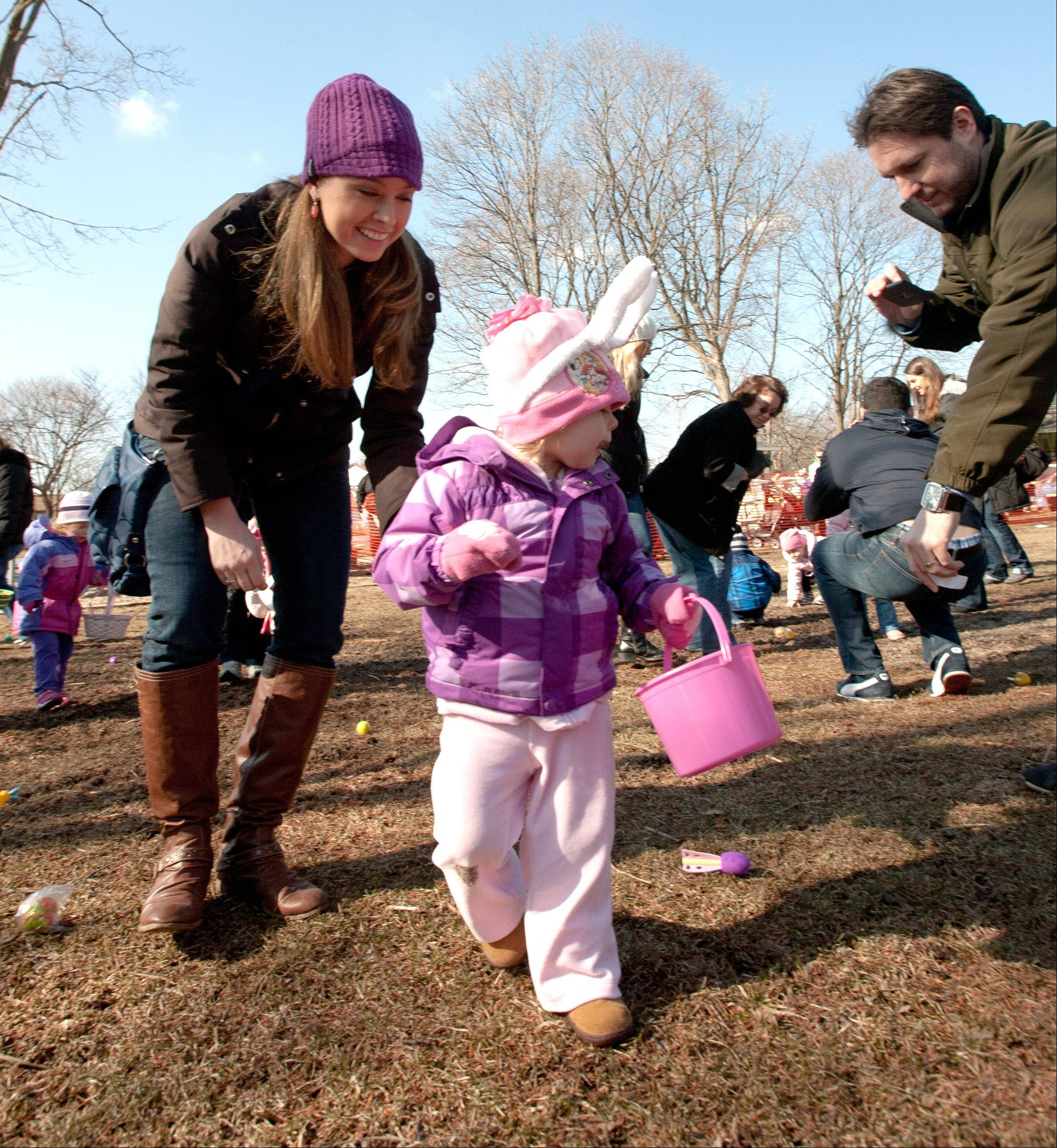 Clara Martyn, 2, of Downers Grove, and her mother Stephanie, fill her bucket during the Wheaton Park District's Great Egg Scramble. Sean Martyn, right, records the moment.