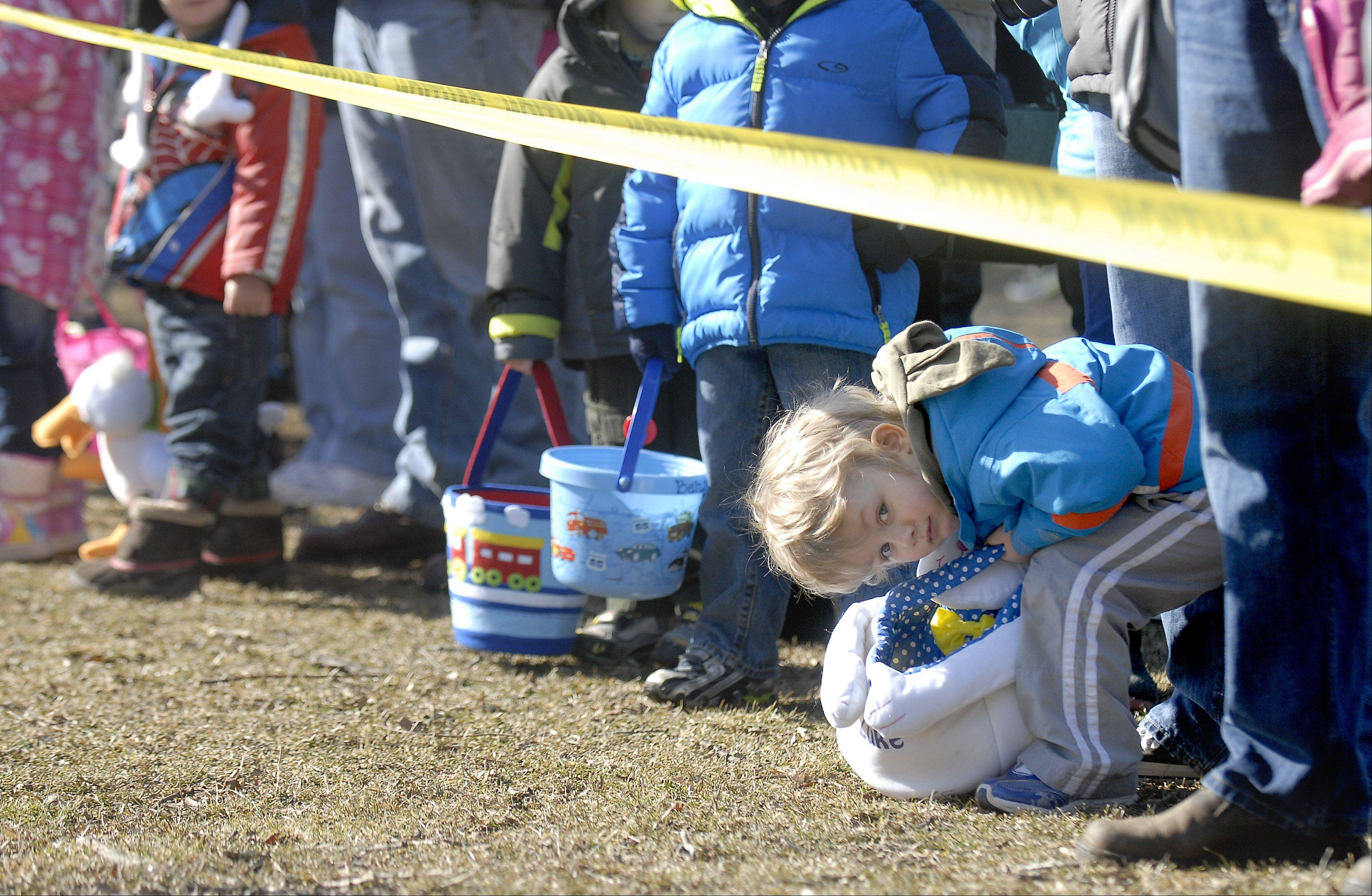 Luke Dooley, 3, of St. Charles, peeks under the yellow caution tape at the starting line of St. Charles Park District's Free Easter Egg Hunt at Pottawatomie Park Saturday. Luke came with his dad, Brian.
