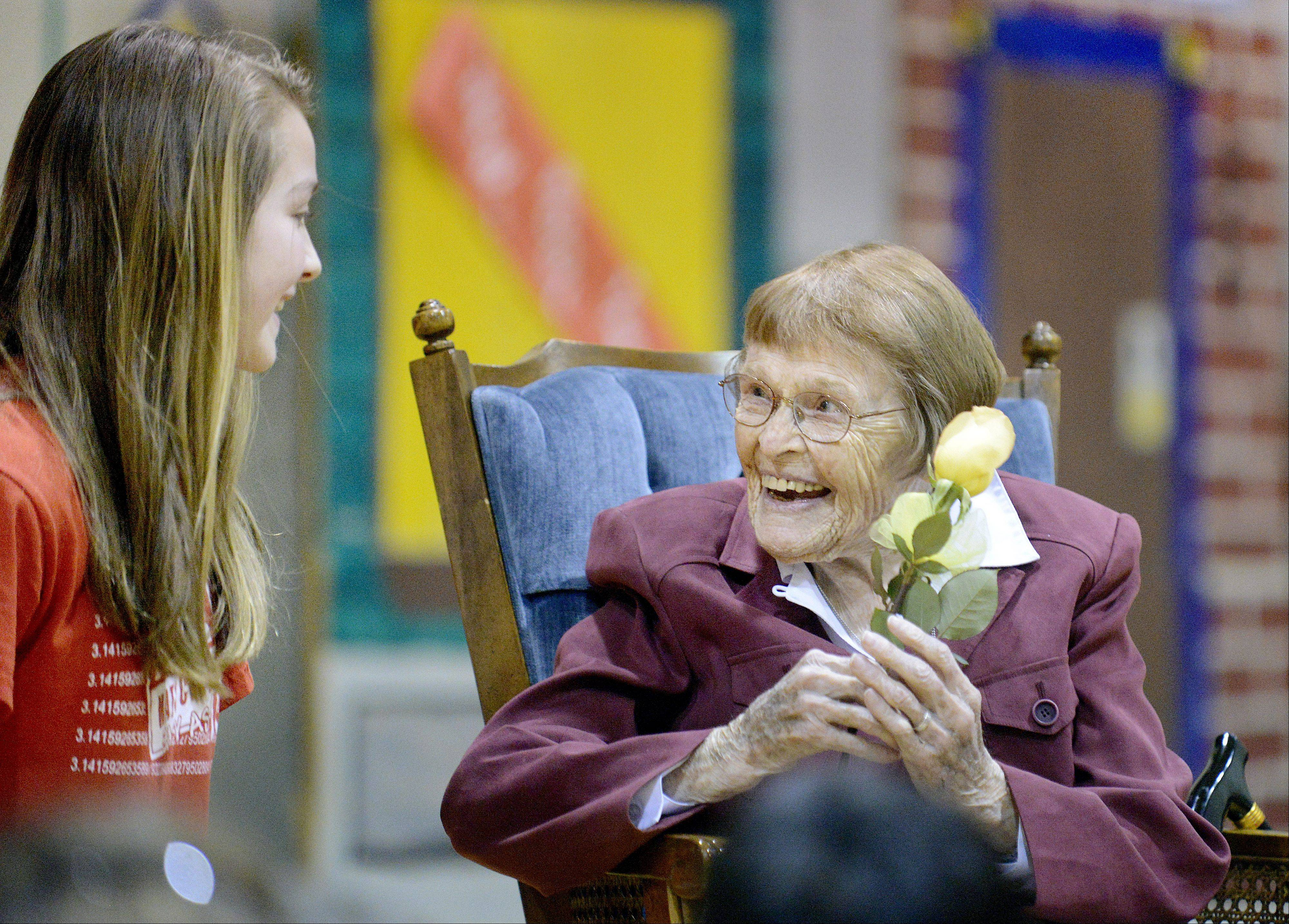 "Sister Johanna Murphy receives a yellow rose from student Abby Phelan, 12, of Geneva, after singing ""When Irish Eyes are Smiling"" for her at her 100th birthday celebration at St. Peter's Catholic Church in Geneva. The song was the most popular of her birth year. Students presented the highlights and news for each decade of her life, and then gave her a rose after each decade, which in turn made a flower bouquet."