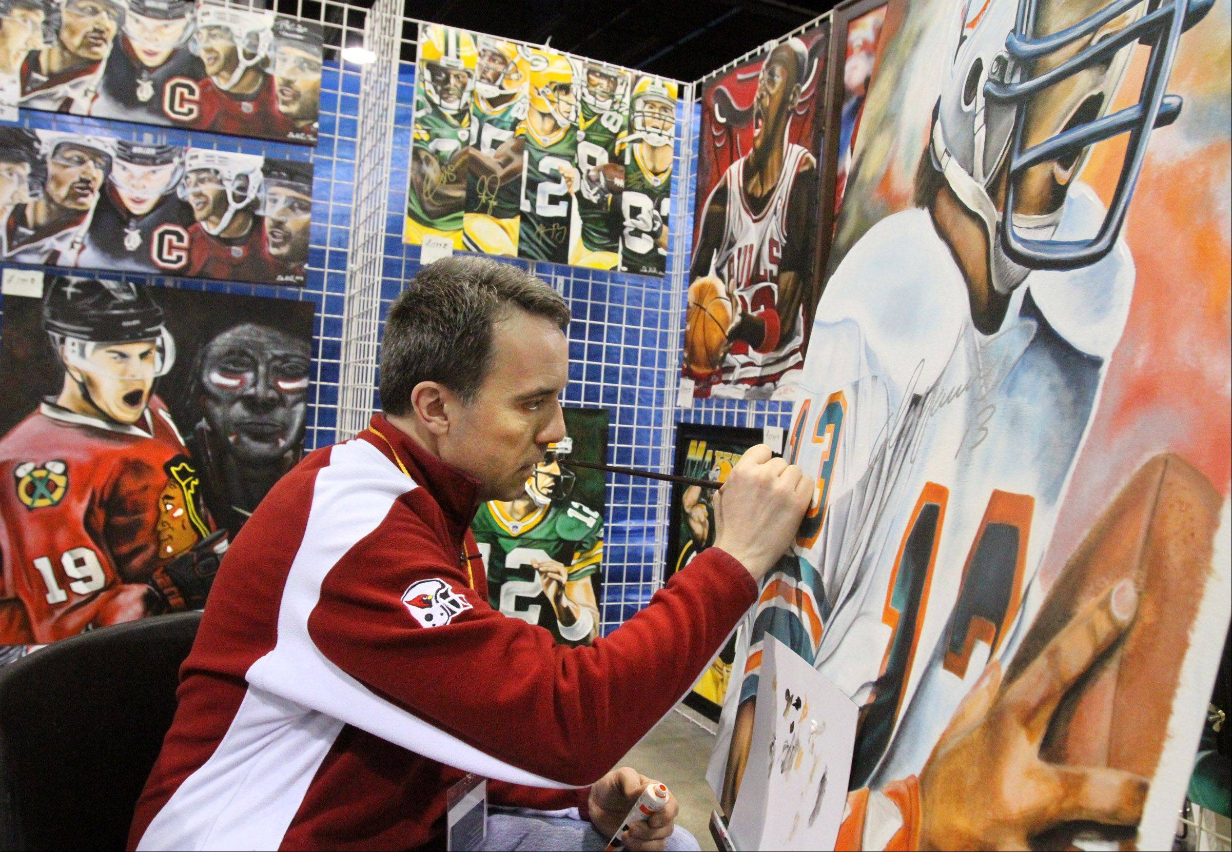 Dan St. Clair, of Davis Junction, Ill., paints sports figures at the 46th annual Sun-Times Sports Collectibles Show Sunday at the Donald E. Stevens Convention Center in Rosemont. St. Clair said his favorite sport to paint is football, and he has painted thousands of pieces.