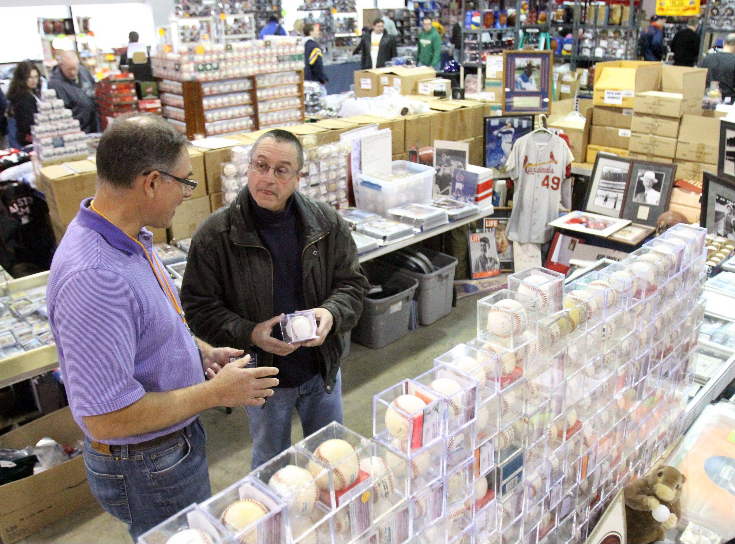 Marc Konny, of Lakewood, right, talks autographed baseballs with sports memorabilia trader Kip Ingle of Atlanta, Georgia during the 46th annual Sun-Times Sports Collectibles Show at Donald E. Stevens Convention Center in Rosemont Sunday.