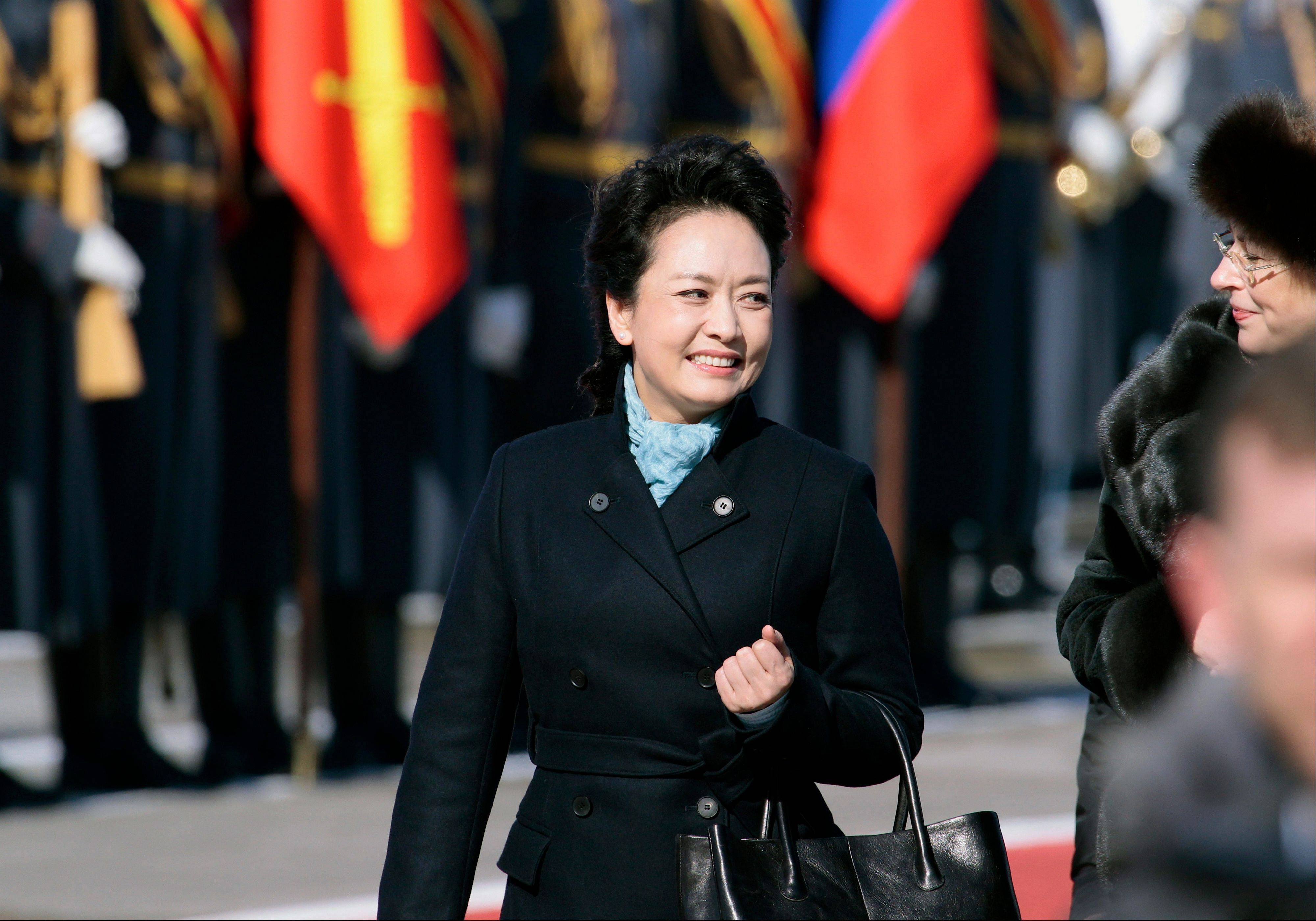 In this March 22, 2013 file photo, Chinese President Xi Jinping's wife Peng Liyuan smiles after arriving at the government airport Vnukovo II, outside Moscow, Russia. New Chinese first lady Peng is emerging as Chinese diplomacy's latest star. A well-known performer on state television, the glamorous Peng was featured prominently on Sunday's state media coverage of President Xi Jinping's activities in Russia. The visit is Xi's first since assuming the presidency earlier this month.