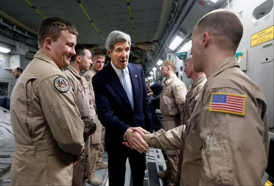 Secretary of State John Kerry, center, shakes hands with a member of the U.S. Air Force 816 Expeditionary Airlift Squadron aboard a C-17 aircraft en route to Baghdad from Amman, Sunday.