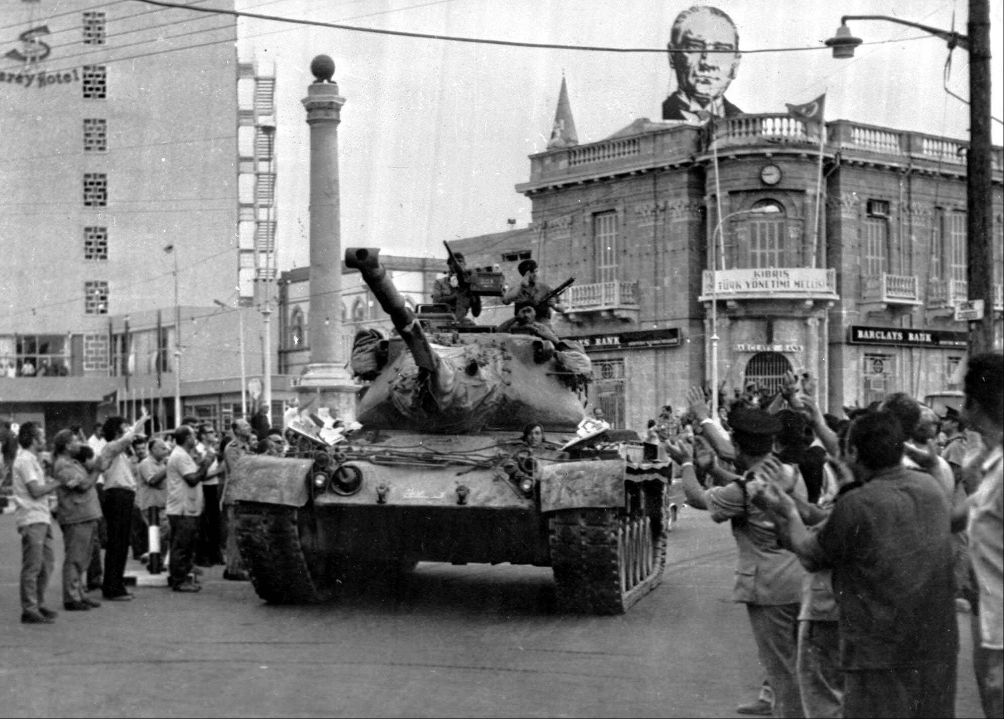 In this 1974 photo a Turkish army tank passes the Saray Hotel in the Turkish section of Nicosia, Cyprus, On the roof of a nearby building is a picture of Kemal Ataturk, founder of the modern Turkish republic.