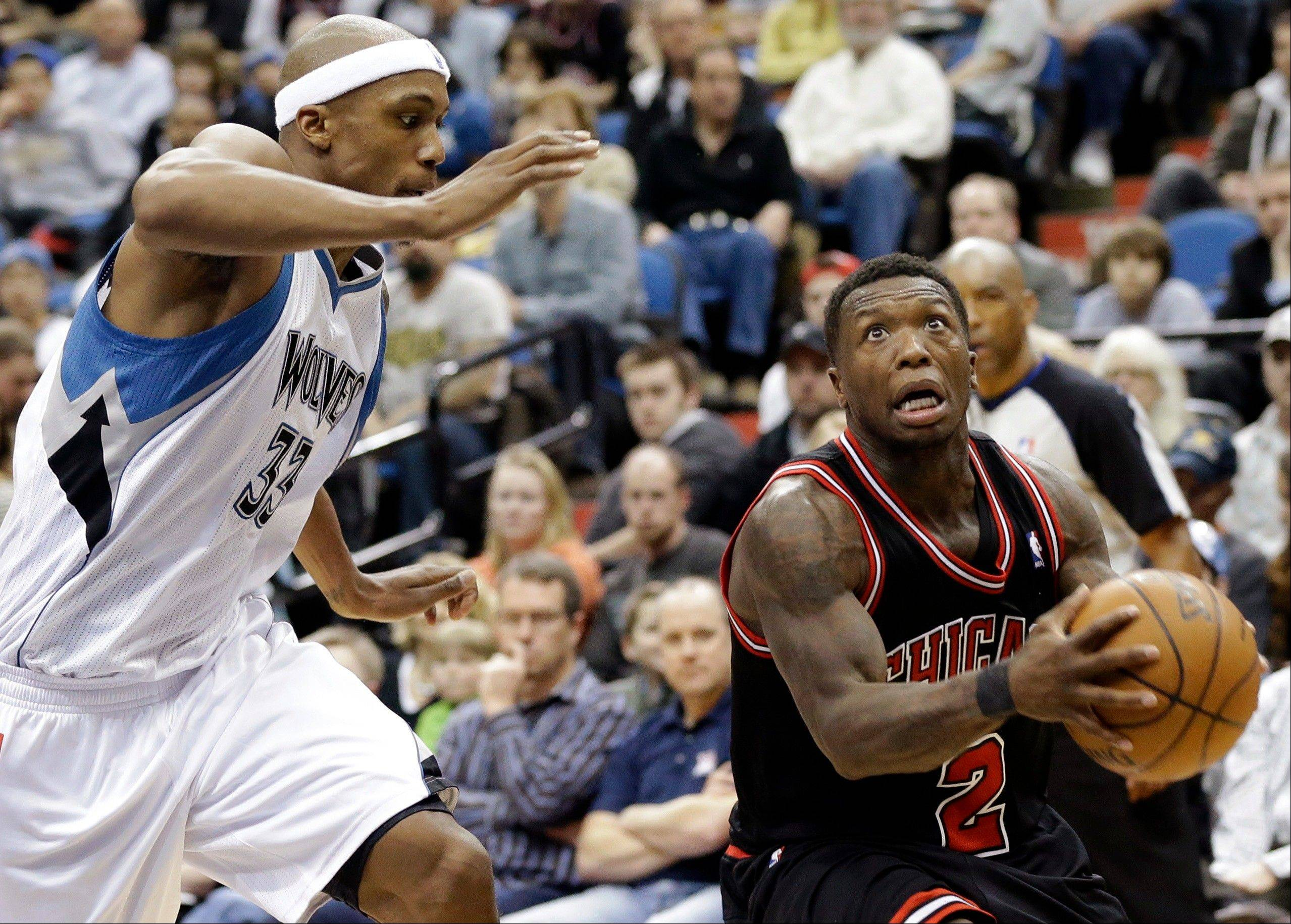 Chicago Bulls' Nate Robinson, right, drives to the basket as Minnesota Timberwolves' Dante Cunningham pursues in the second half of an NBA basketball game, Sunday, March 24, 2013, in Minneapolis. The Bulls won 104-97.