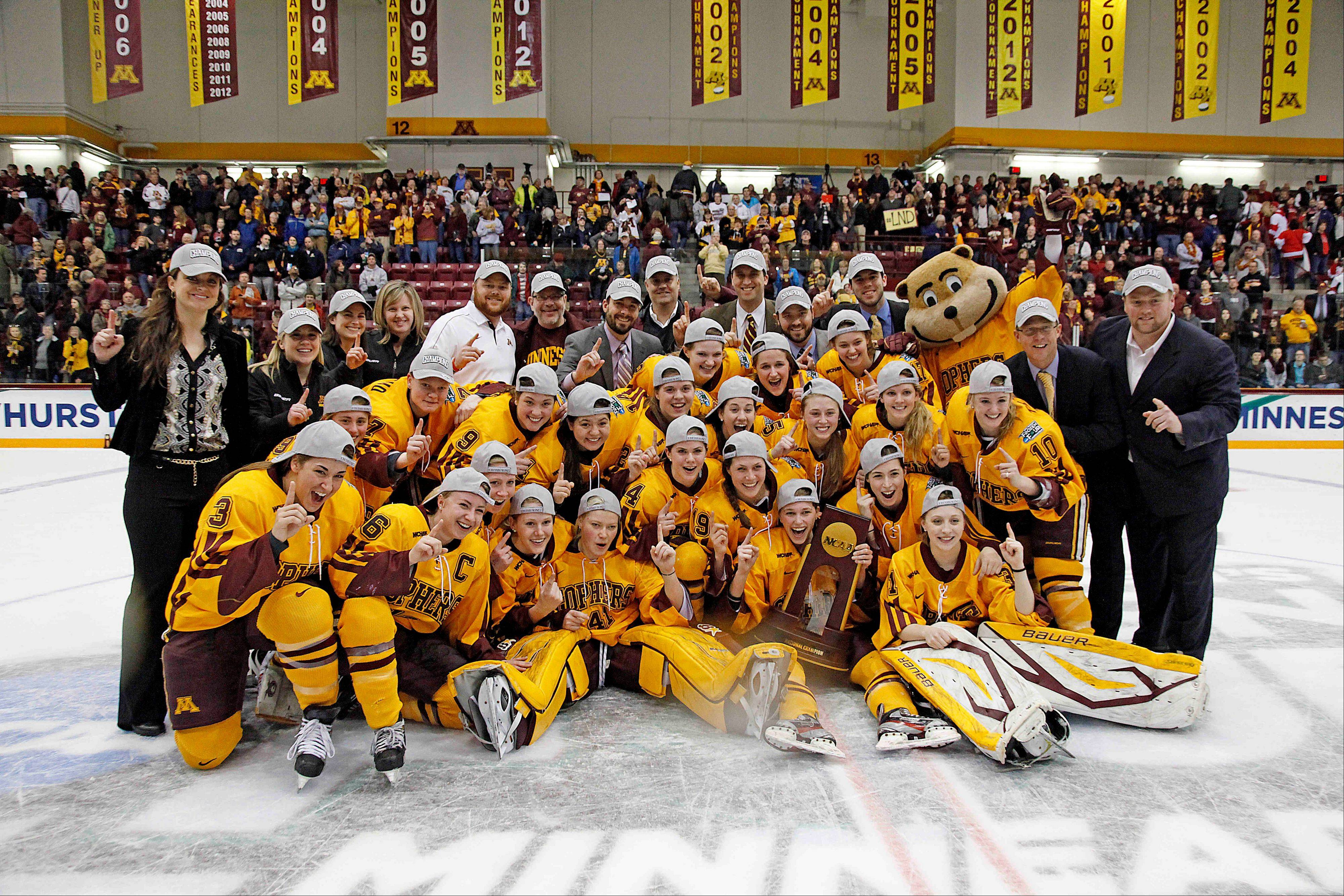 The Minnesota women's hockey team poses with their trophy after their 6-3 win against Boston University in the Frozen Four NCAA Championship college hockey game Sunday in Minneapolis.