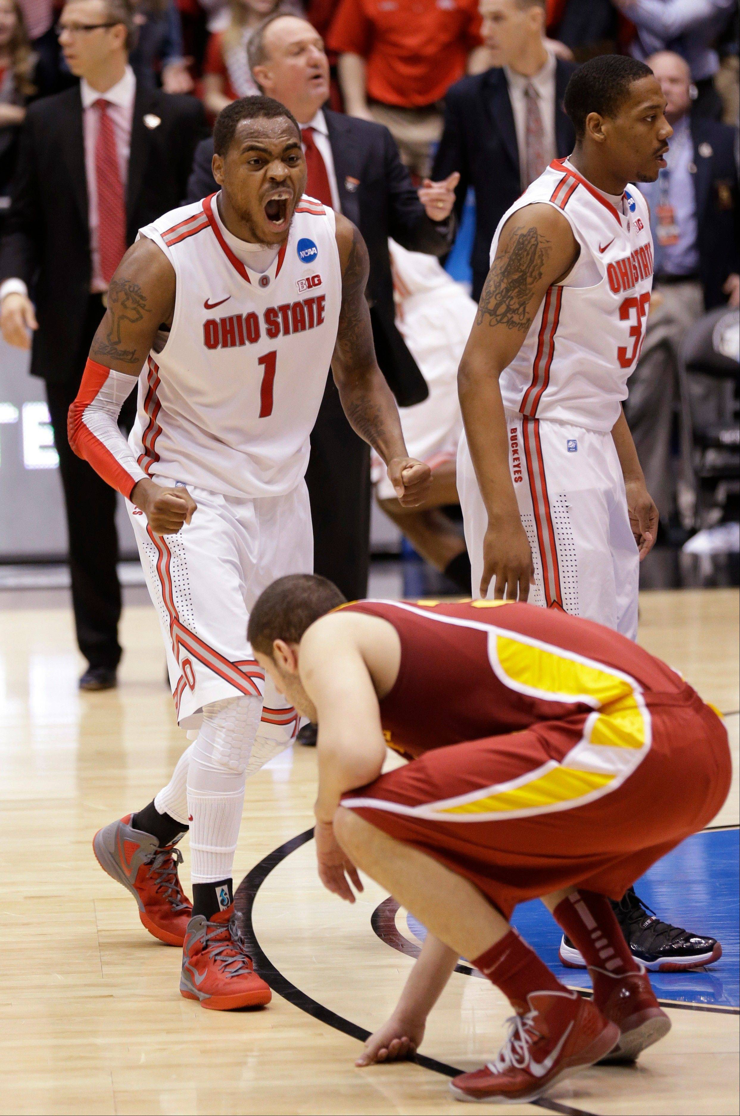 Iowa State forward Georges Niang squats on the floor as Ohio State forward Deshaun Thomas (1) and Lenzelle Smith, Jr. (32) celebrate Sunday in the final moments of Ohio State's 78-75 win in a third-round game of the NCAA tournament in Dayton, Ohio.