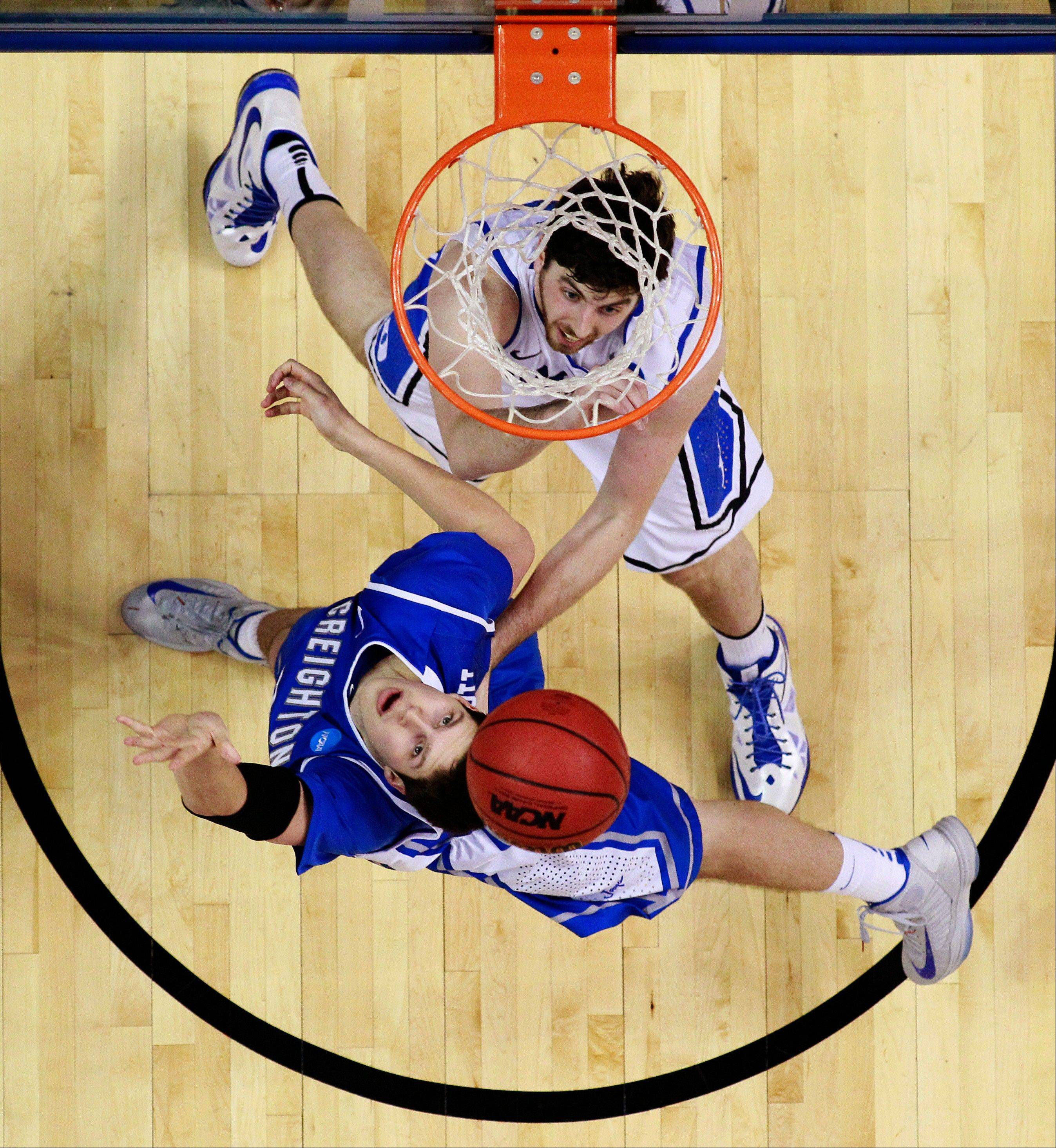 Creighton's Doug McDermott, bottom, shoots against Duke's Ryan Kelly during the second half of a third-round game of the NCAA college basketball tournament, Sunday, March 24, 2013, in Philadelphia.