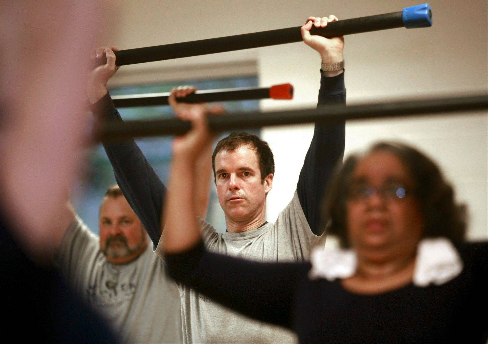 Dr. Ben Fischer, center, works out with patients at the YMCA in Raleigh, N.C. Fischer meets his patients at the gym, working out with men and women who have committed to a healthier lifestyle.