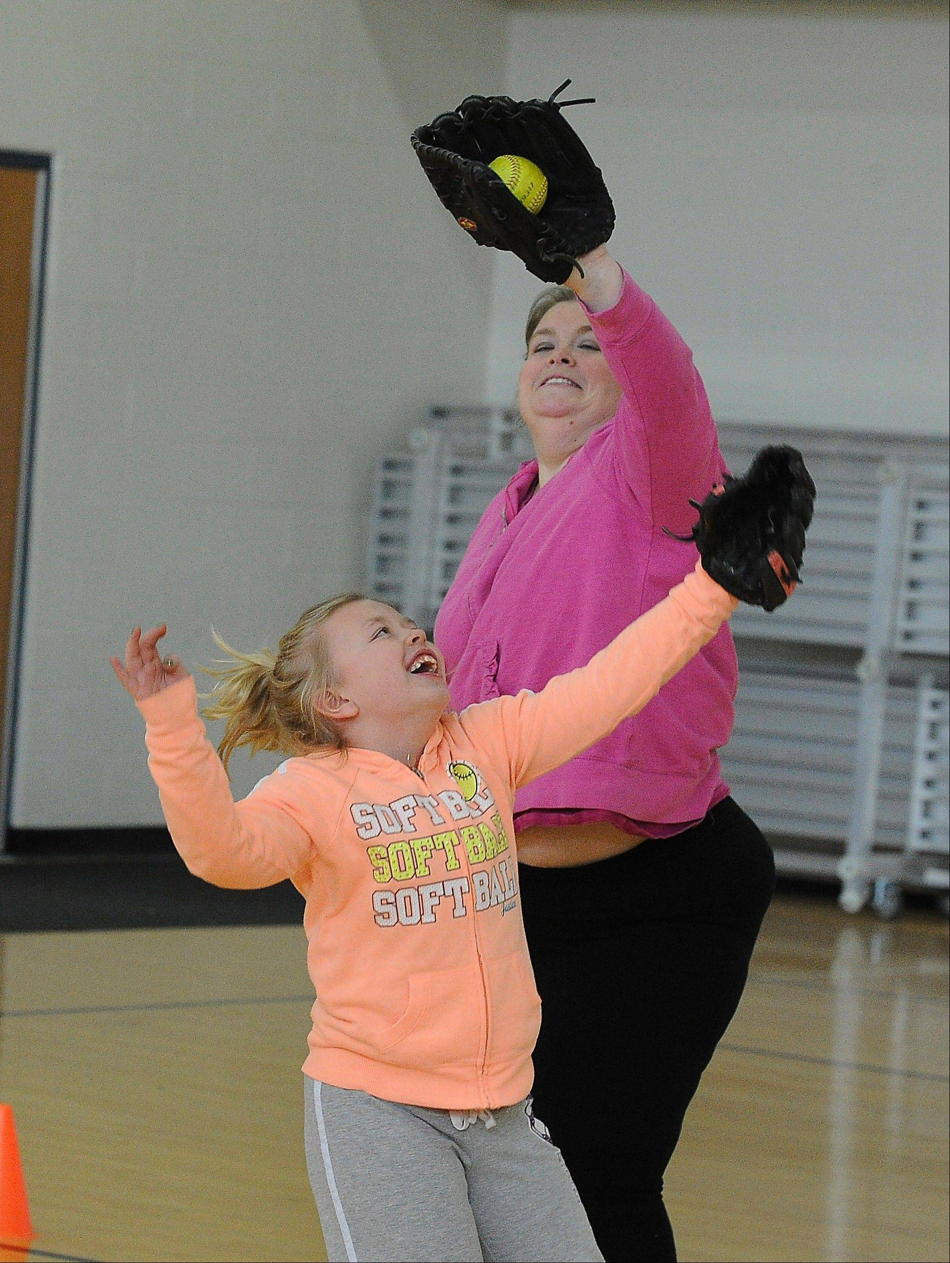 Megan McCarthy-Cook and her daughter, 8-year-old Molly, play catch at the Hoffman Estates Park District gym.