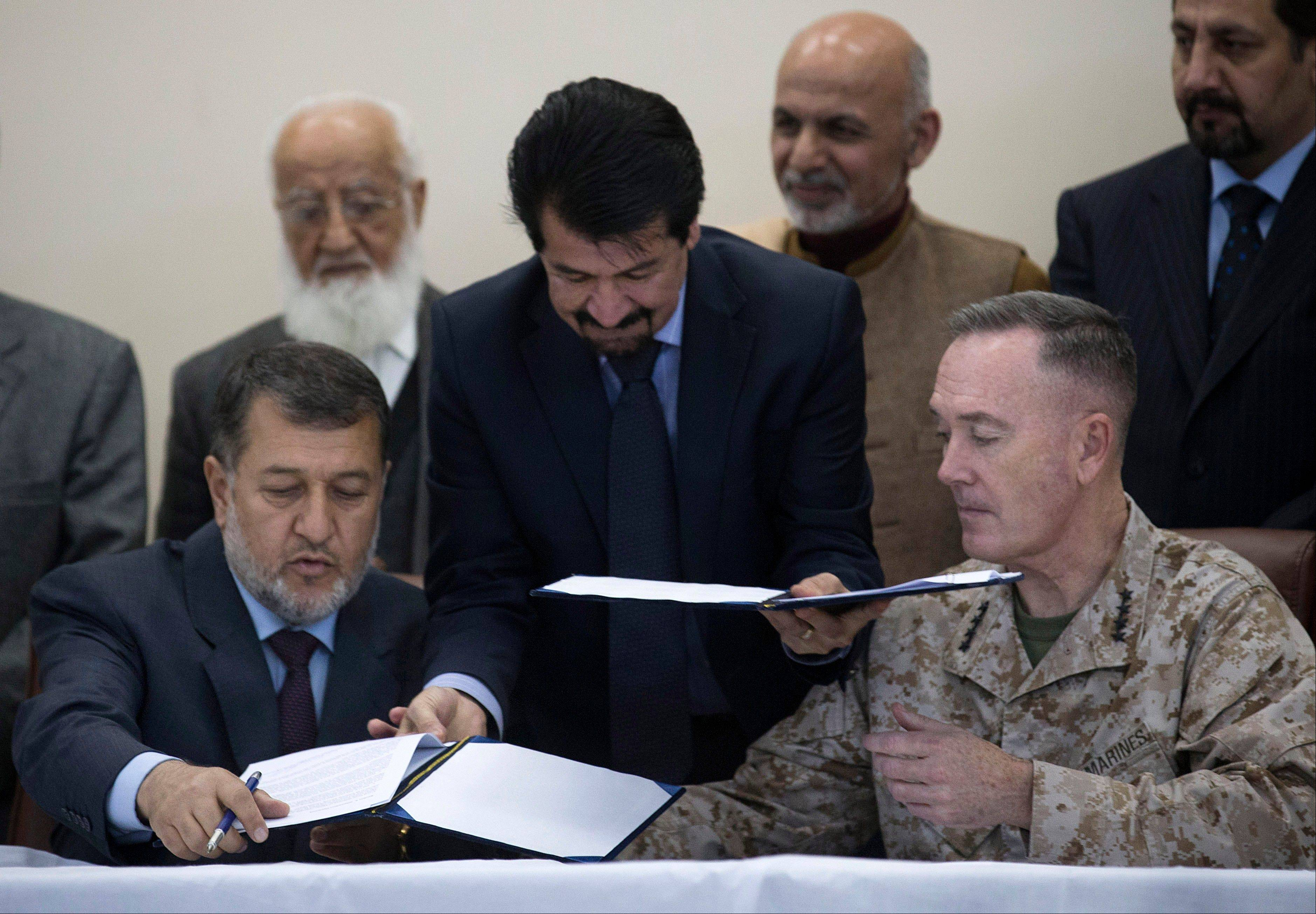 Afghan Defense Minister General Bismillah Khan, left, signs the papers to hand over the Parwan Detention Facility to Afghan authorities with top U.S. commander in Afghanistan General Joseph Dunford in Bagram, outside Kabul, Afghanistan, Monday.