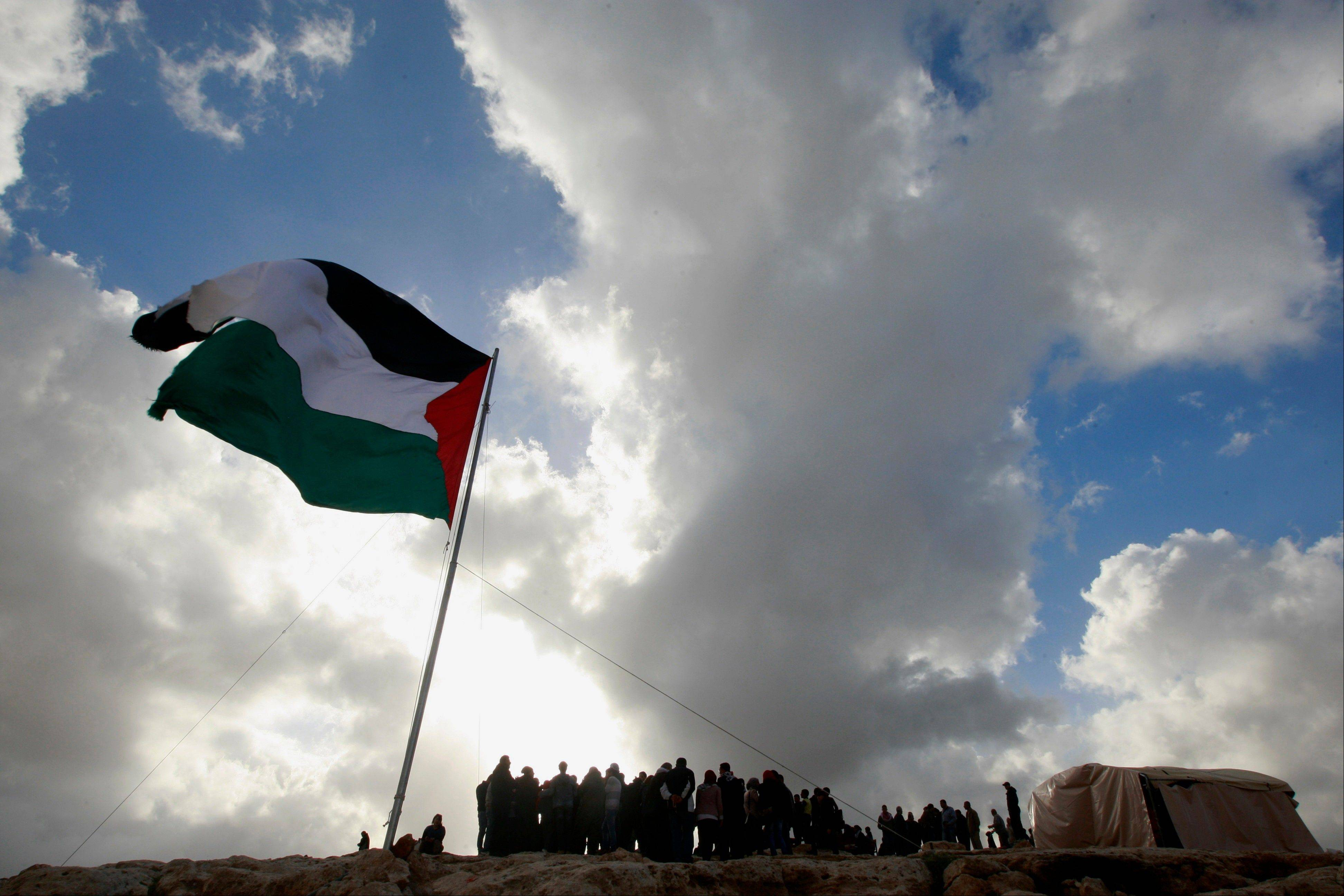 A Palestinian flag flies by a tent set up by activists in an area known as E1, near Jerusalem, Saturday.