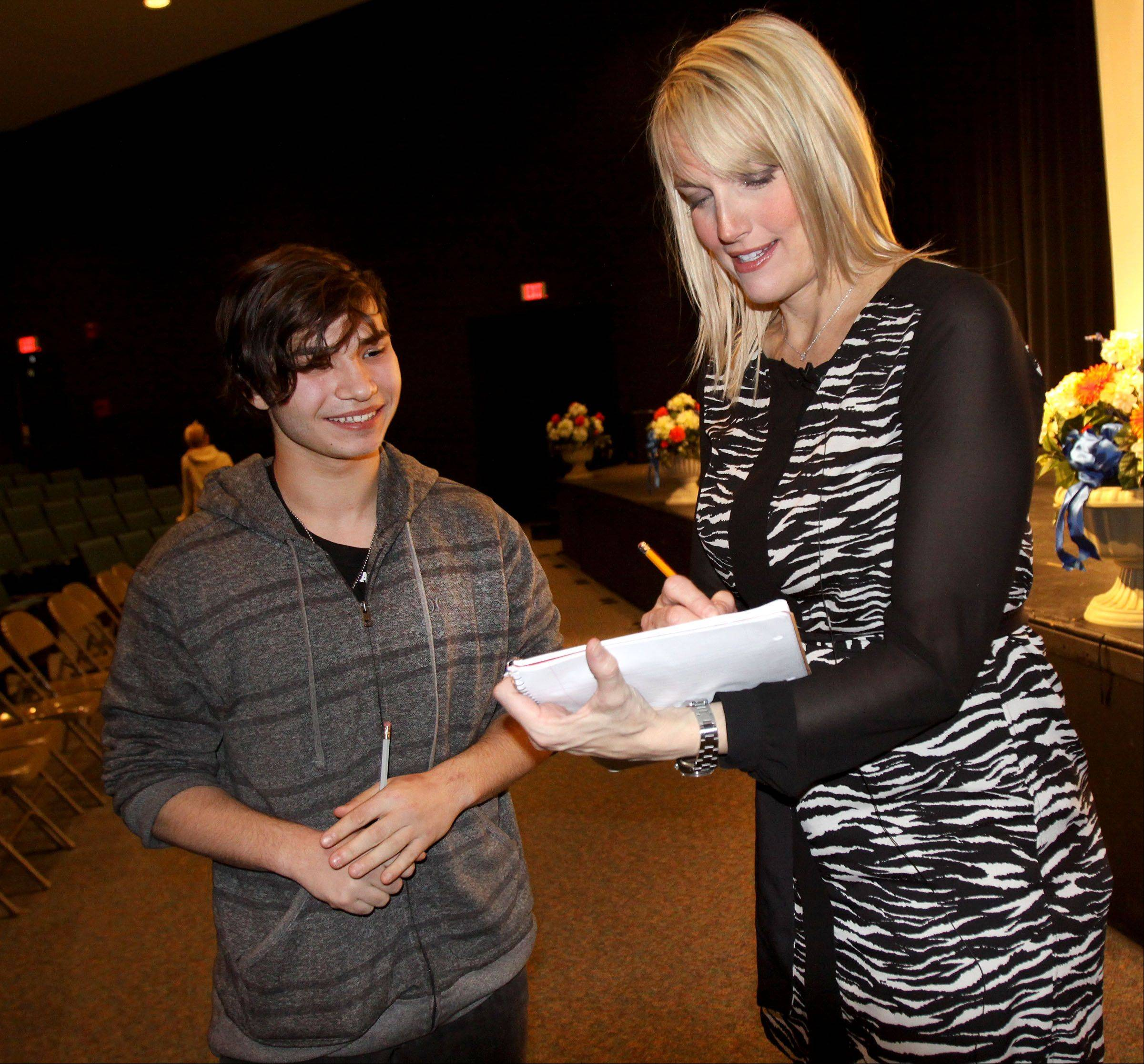 "Sophomore Ben Asire gets an autograph from HGTV's Monica Pedersen Friday after Fenton High School inducted her as a member of its Wall of Fame. A 1988 graduate of Fenton, Pedersen is an interior designer on shows such as ""Designed to Sell"" and ""Bang for Your Buck."""