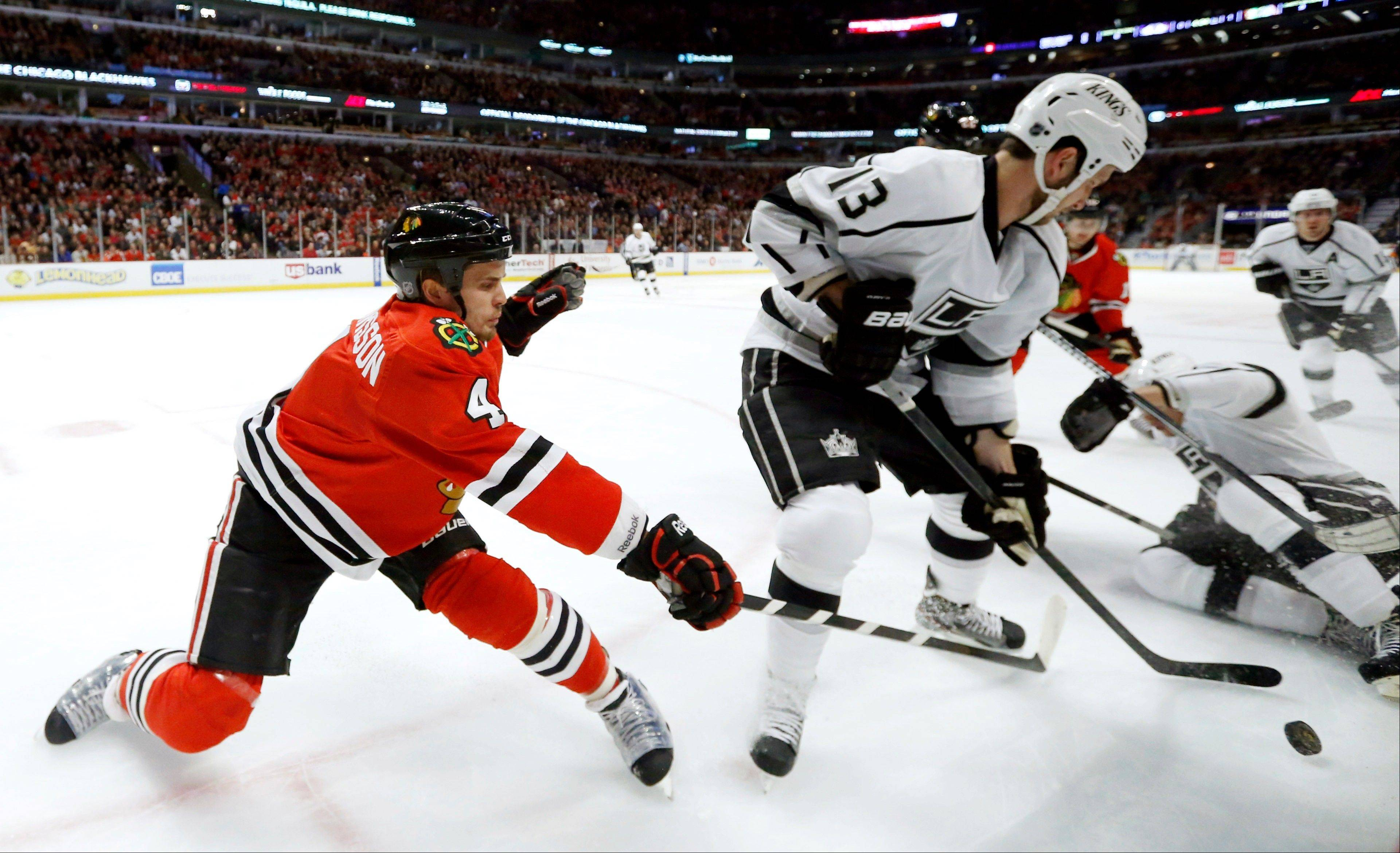 Chicago Blackhawks defenseman Niklas Hjalmarsson (4), of Sweden, battles Los Angeles Kings center Tyler Toffoli for a loose puck during the first period of an NHL hockey game, Monday, March 25, 2013, in Chicago.