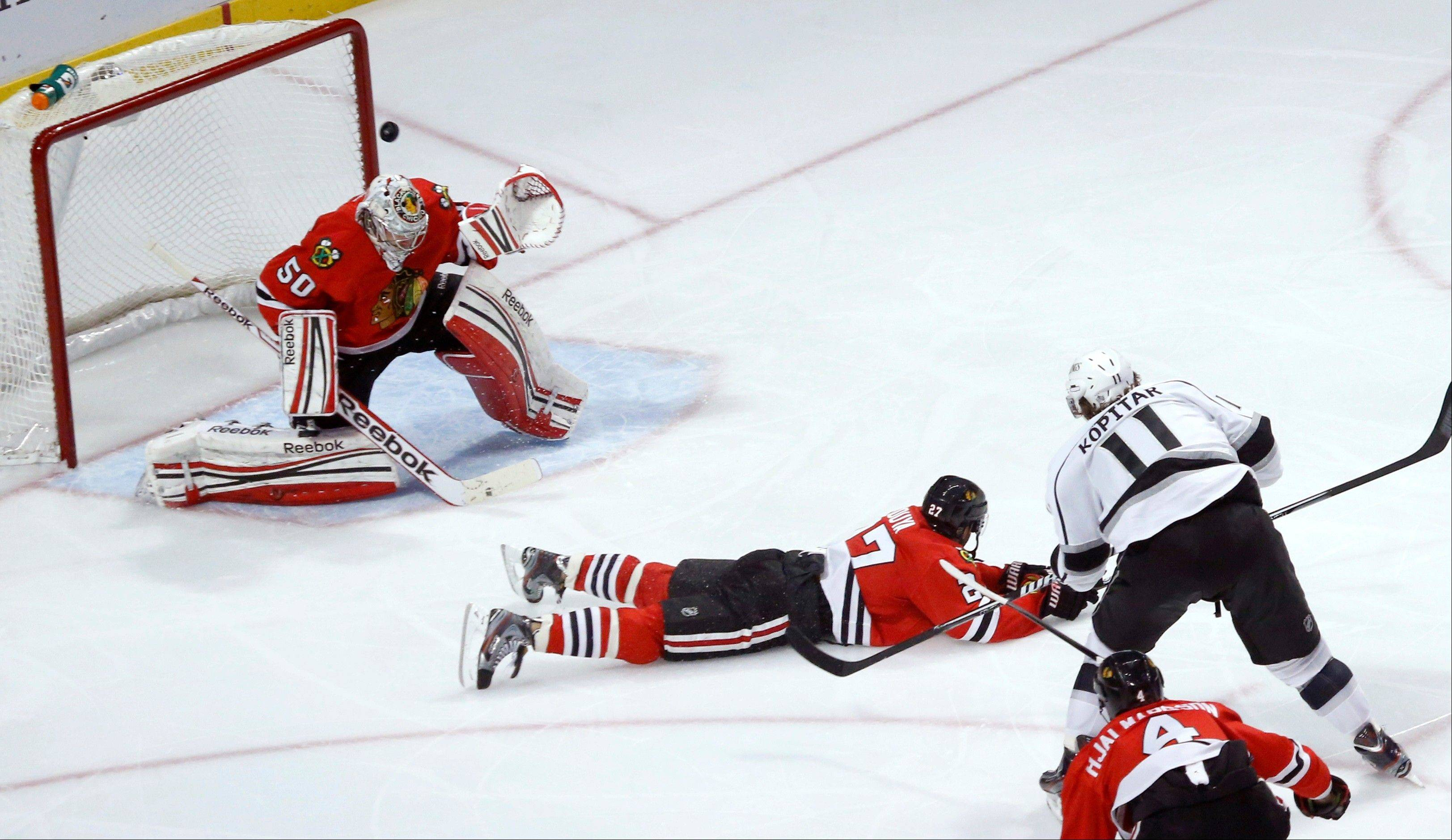 Los Angeles Kings center Anze Kopitar (11), from Slovenia, shoots and scores past Chicago Blackhawks defenseman Johnny Oduya (27), of Sweden, and goalie Corey Crawford (50) during the second period of an NHL hockey game, Monday, March 25, 2013, in Chicago. (AP Photo/Charles Rex Arbogast)