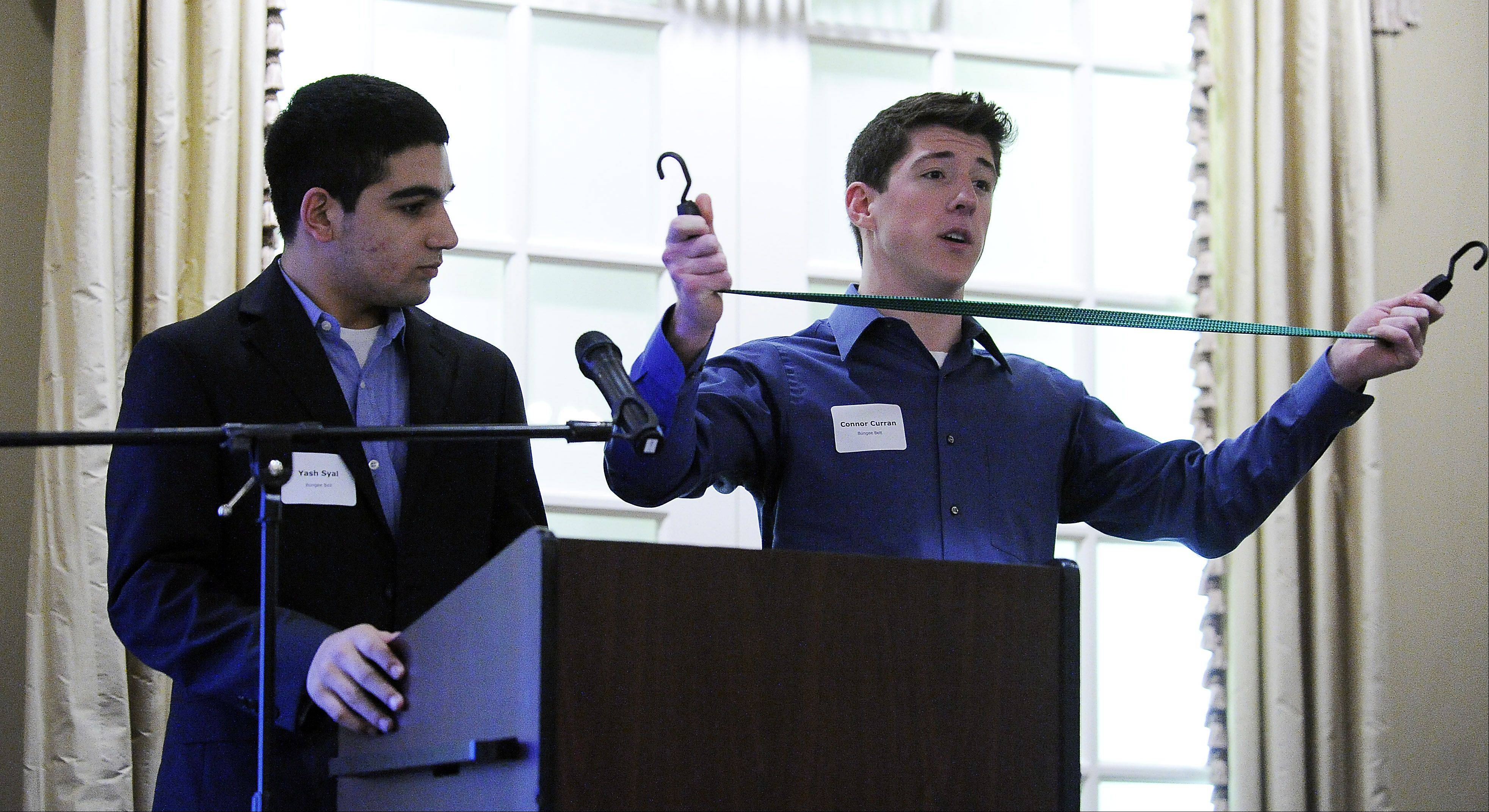 Yash Syal, 16, of Palatine High School, left, and his business partner Connor Curran, 17, of St. Viator High School demonstrate their concept for Bungee Belts at the Palatine Area Chamber of Commerce and District 211 Young Entrepreneurs Academy. They were pitching their product to potential investors.