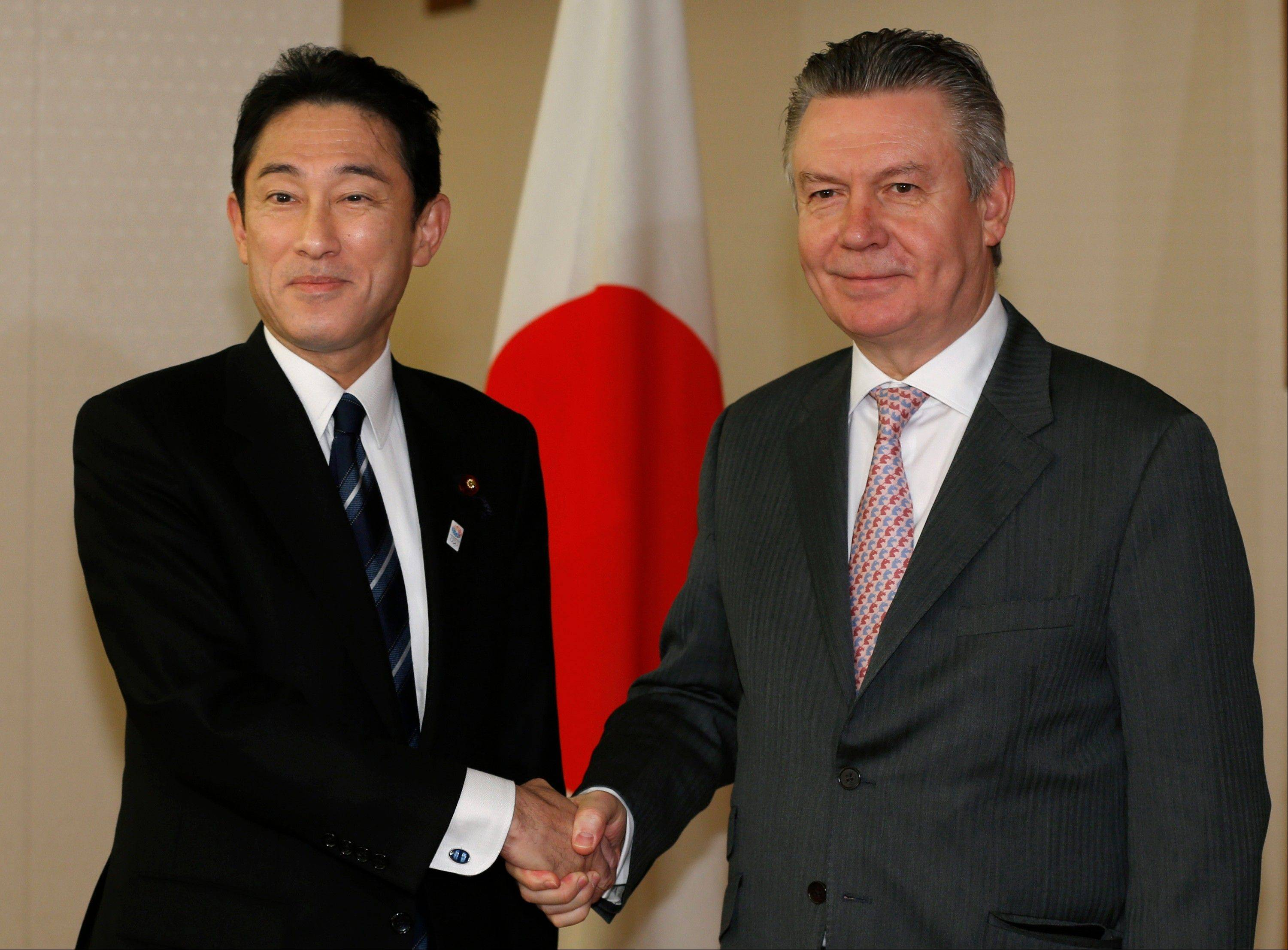 European Trade Commissioner Karel De Gucht, right, and Japanese Foreign Minister Fumio Kishida pose for photographers Monday prior to their meeting at the Foreign Ministry in Tokyo. De Gucht is in Tokyo and meeting with Japanese government and business officials as scheduled.