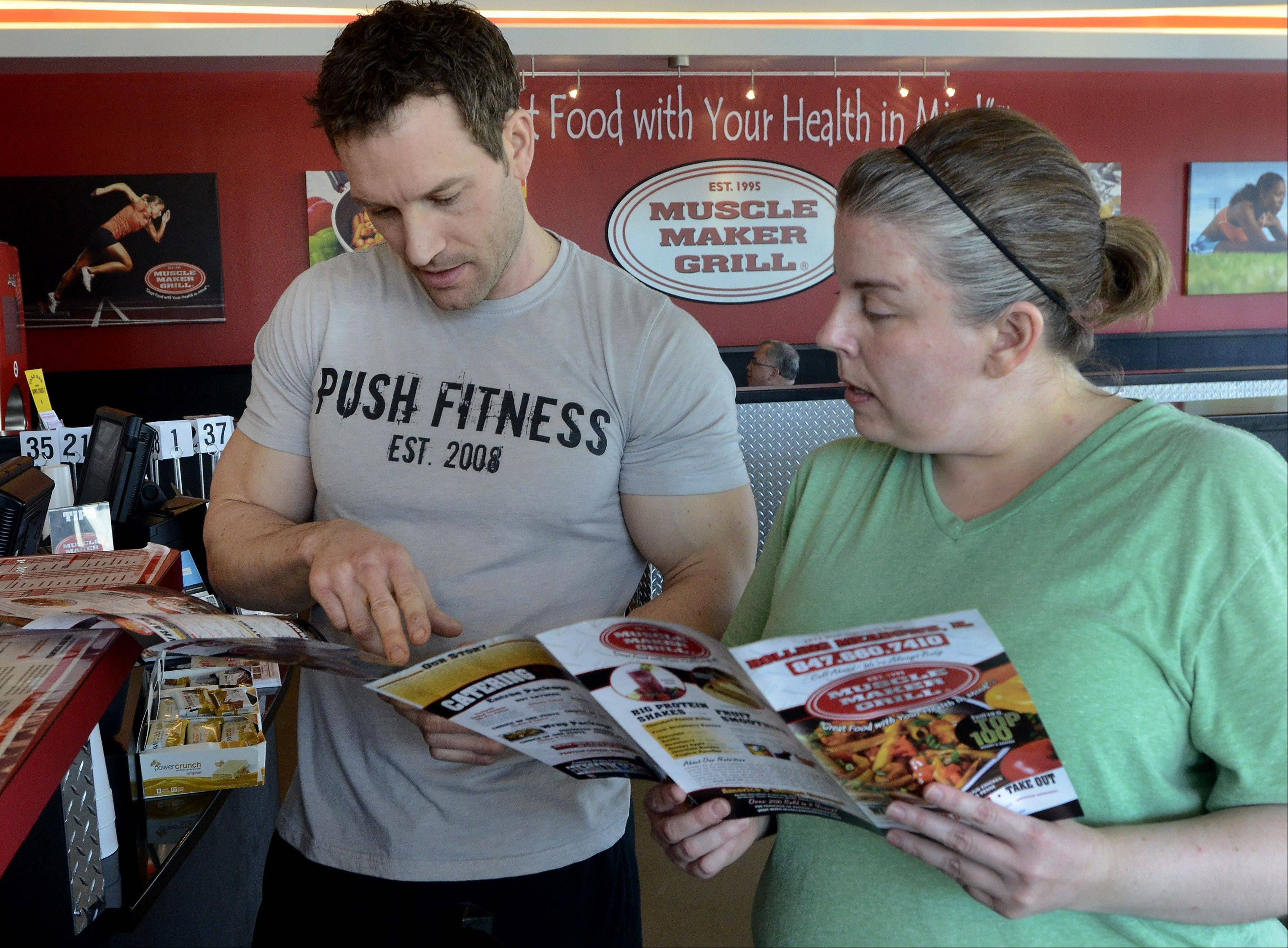 Joshua Steckler helps Melynda Findlay navigate the menu at Muscle Maker Grill in Rolling Meadows.