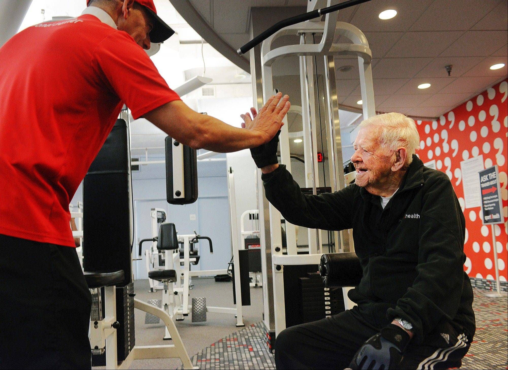 Ray Clark gets a high-five from his trainer, Thom Hunter, who is 70; Clark started going to the gym when he was 98.