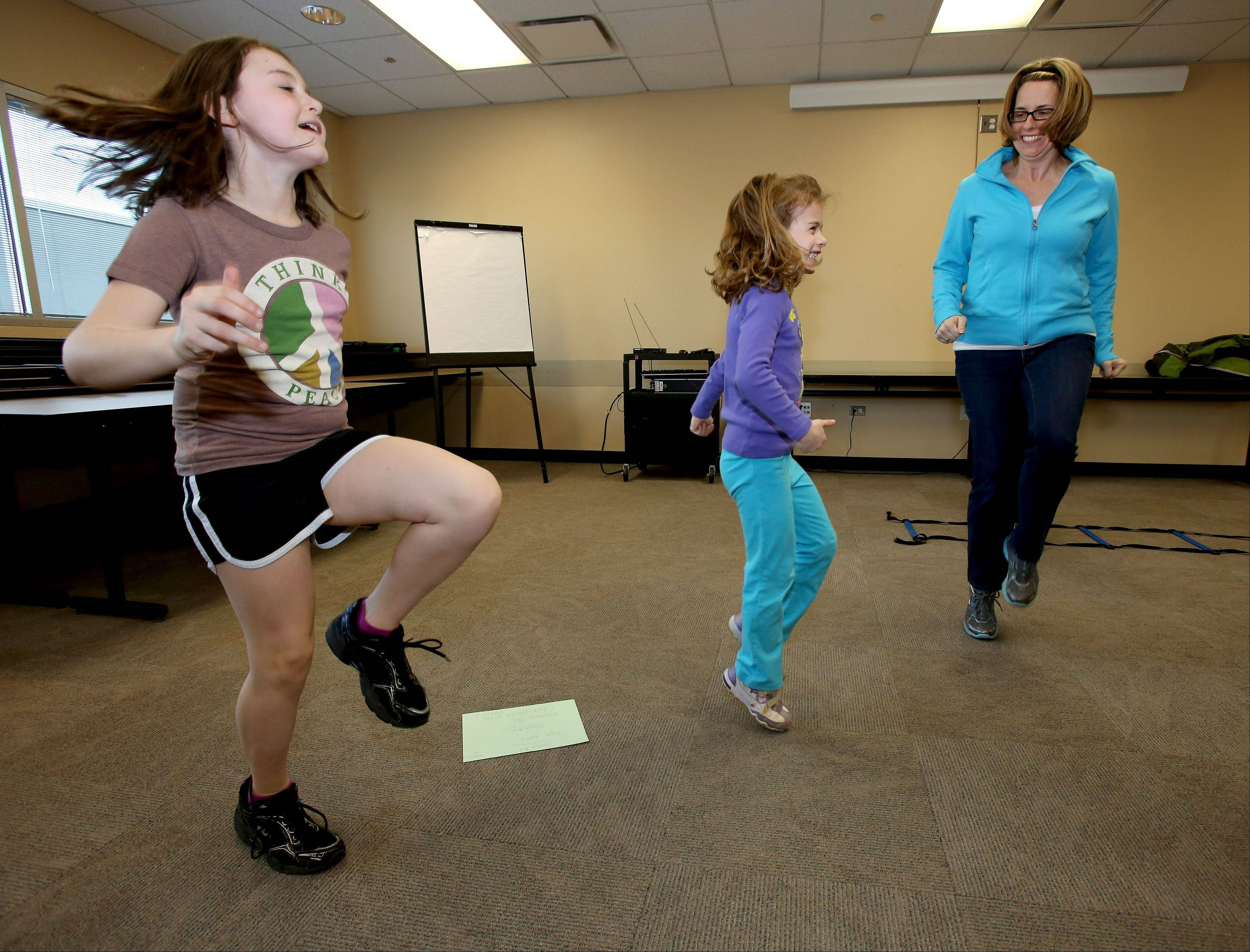 Maddie Maci, 8, and her sister Mackenzie, 4, do high knee lifts with their mother, Molly Maci of Downers Grove, as they participate in the ProActive Kids program at the Advocate Good Samaritan Health and Wellness Center in Downers Grove.