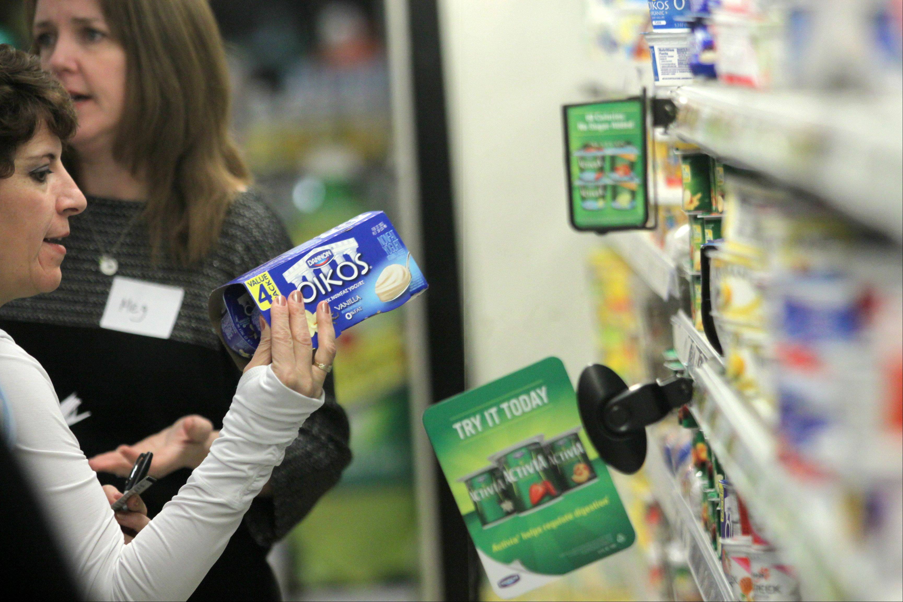 Martha Rodriguez of Streamwood, translator for the Fit Kids program offered by Alexian Brothers' pediatric department, studies nutrition facts on yogurt during a recent meeting at a Jewel in Schaumburg.