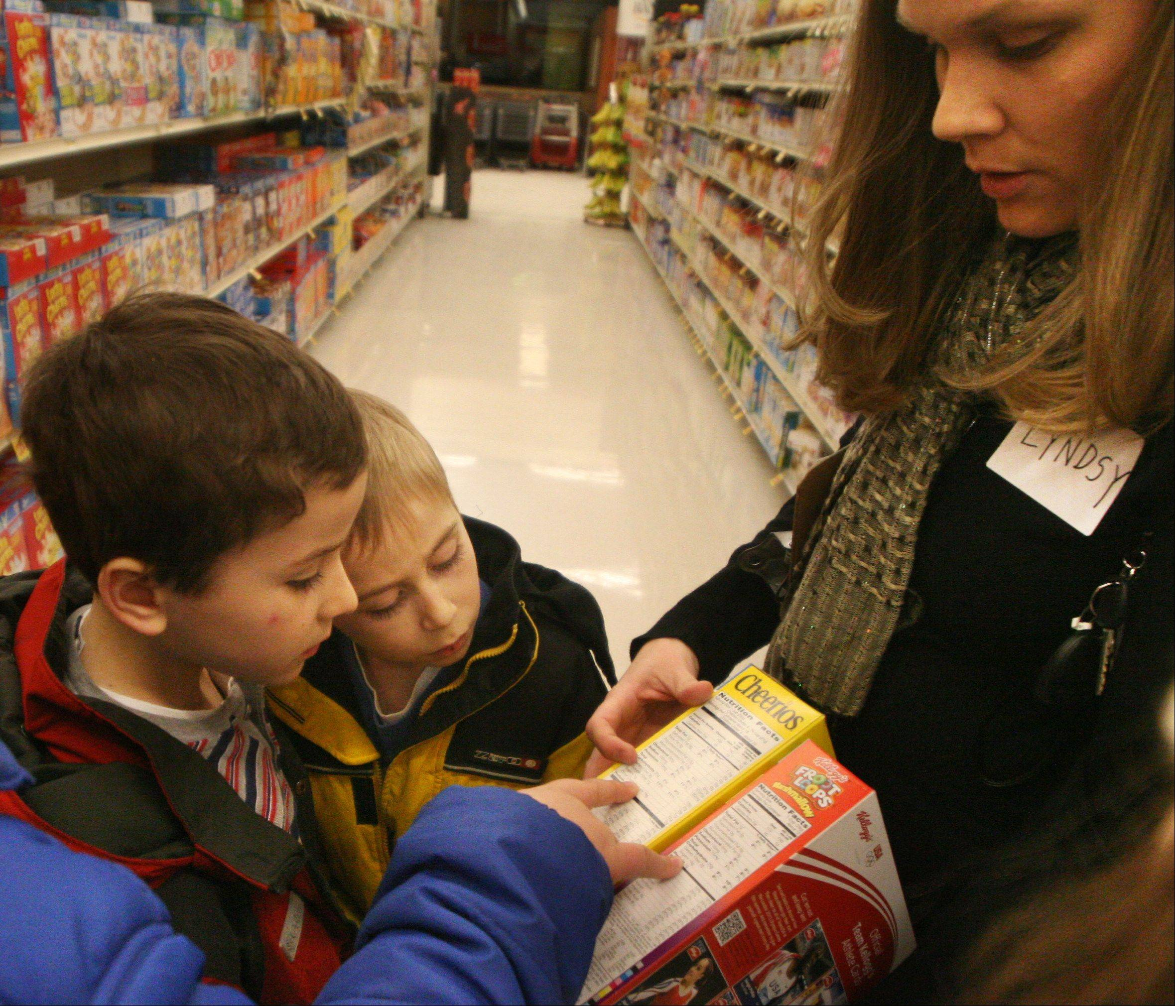 Matthew Toniolo, 7, and his bother Jacob, 9, of Bartlett, compare nutrition facts on cereal boxes with program instructor Lyndsy Eltman at a Jewel in Schaumburg during a meeting of the Alexian Brothers Fit Kids program. The grocery store trip focuses on learning to read food labels critically.