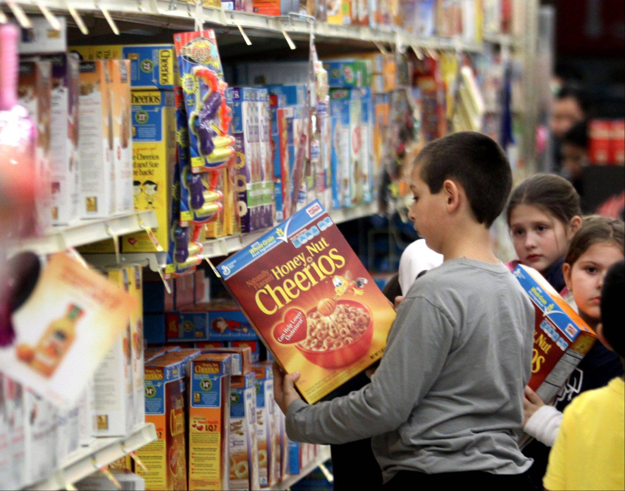 Seth Golz, 8, of Roselle, examines nutrition facts on a cereal box at Jewel in Schaumburg during a meeting of the Alexian Brothers Fit Kids program.