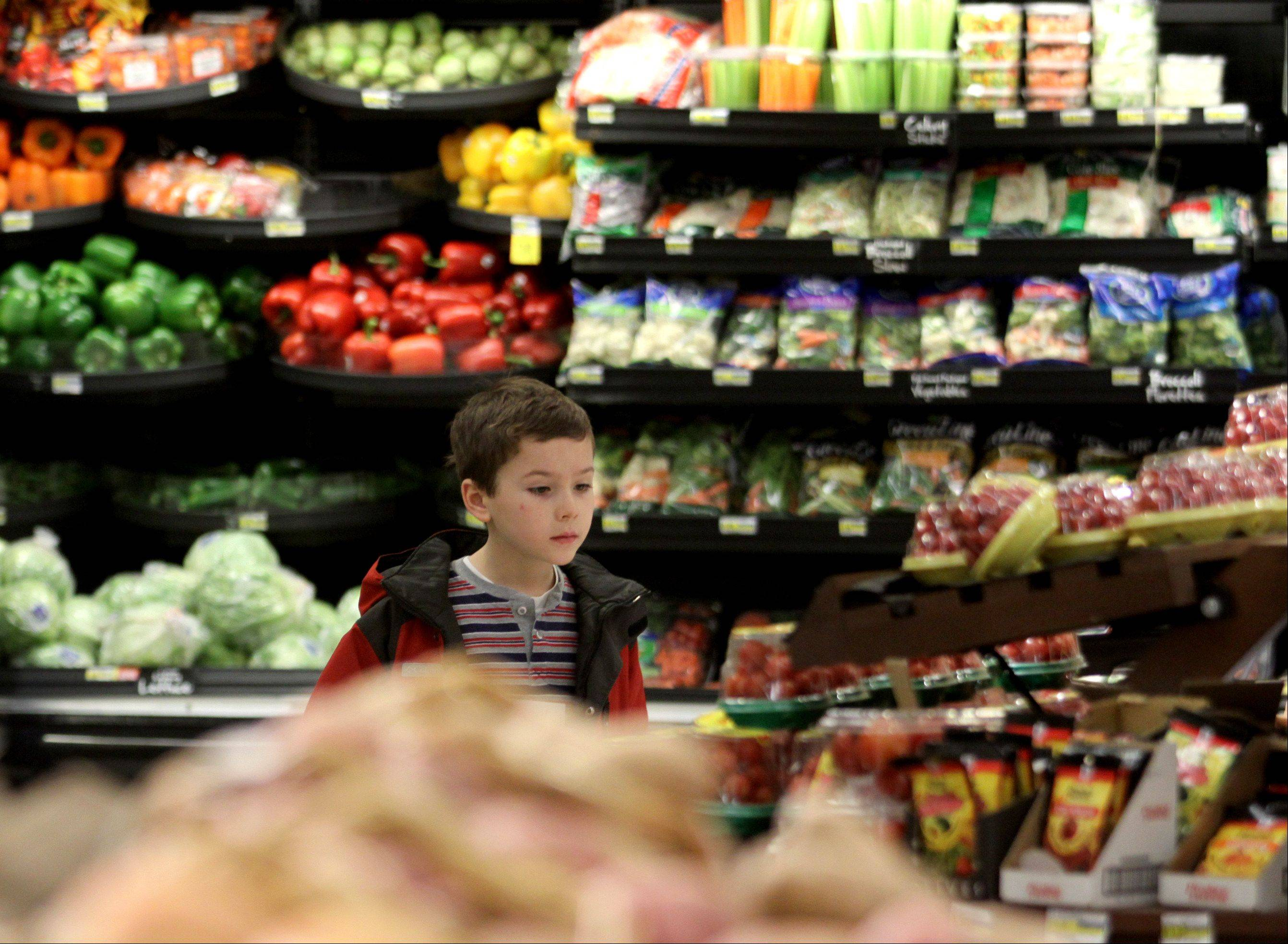 Matthew Toniolo, 7, of Bartlett, examines fresh produce options at a Jewel in Schaumburg during a meeting of the Fit Kids run by Alexian Brothers' Pediatric Department.