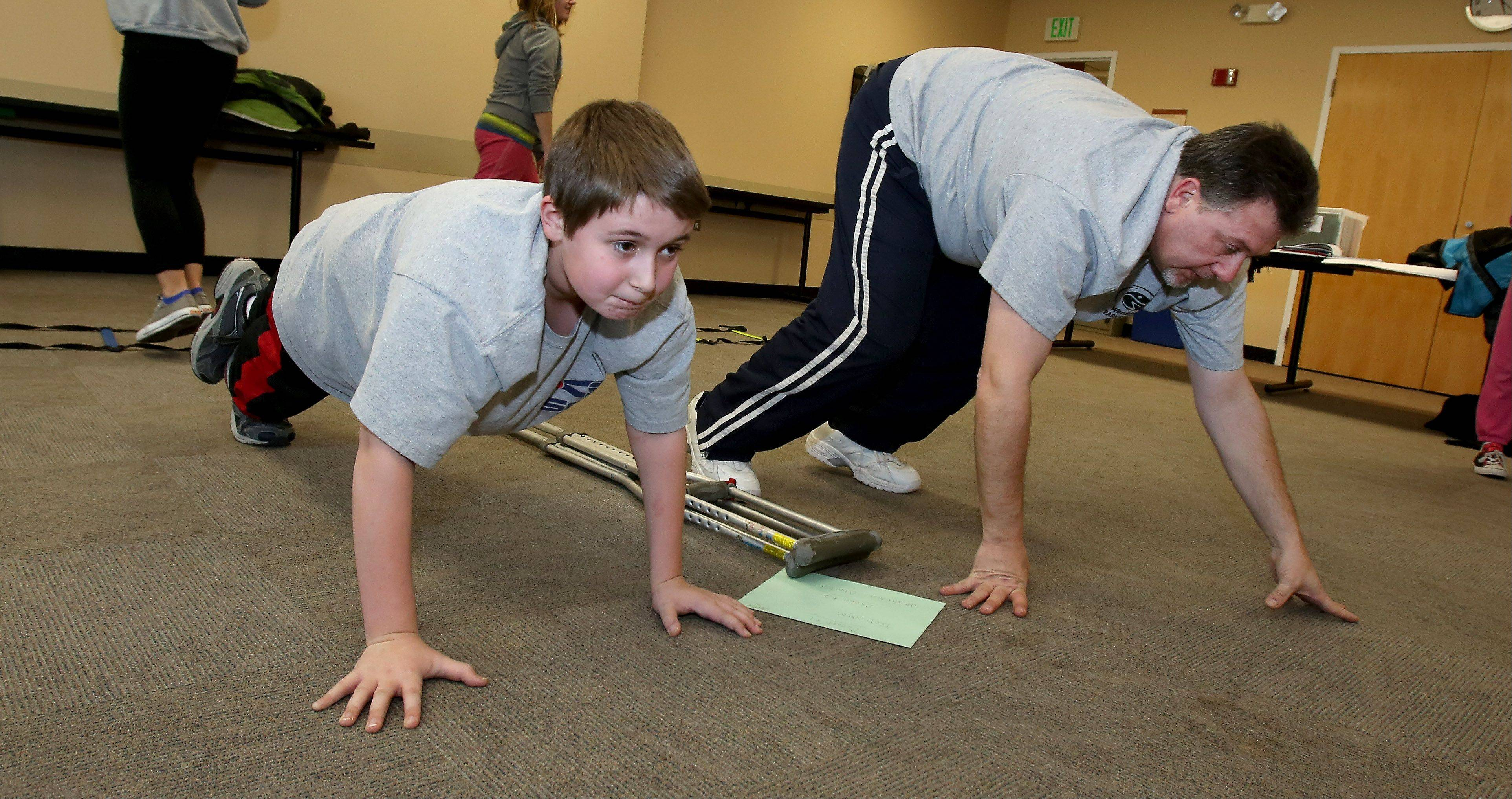 Marcus Wright, 10, of Westmont, works out with his mother, Dio, under the guidance of Jennifer Tewell, program coordinator and lifestyle coach with ProActive Kids. The Wright family is participating in the ProActive Kids program offered for the first time this year at the Advocate Good Samaritan Health and Wellness Center in Downers Grove.