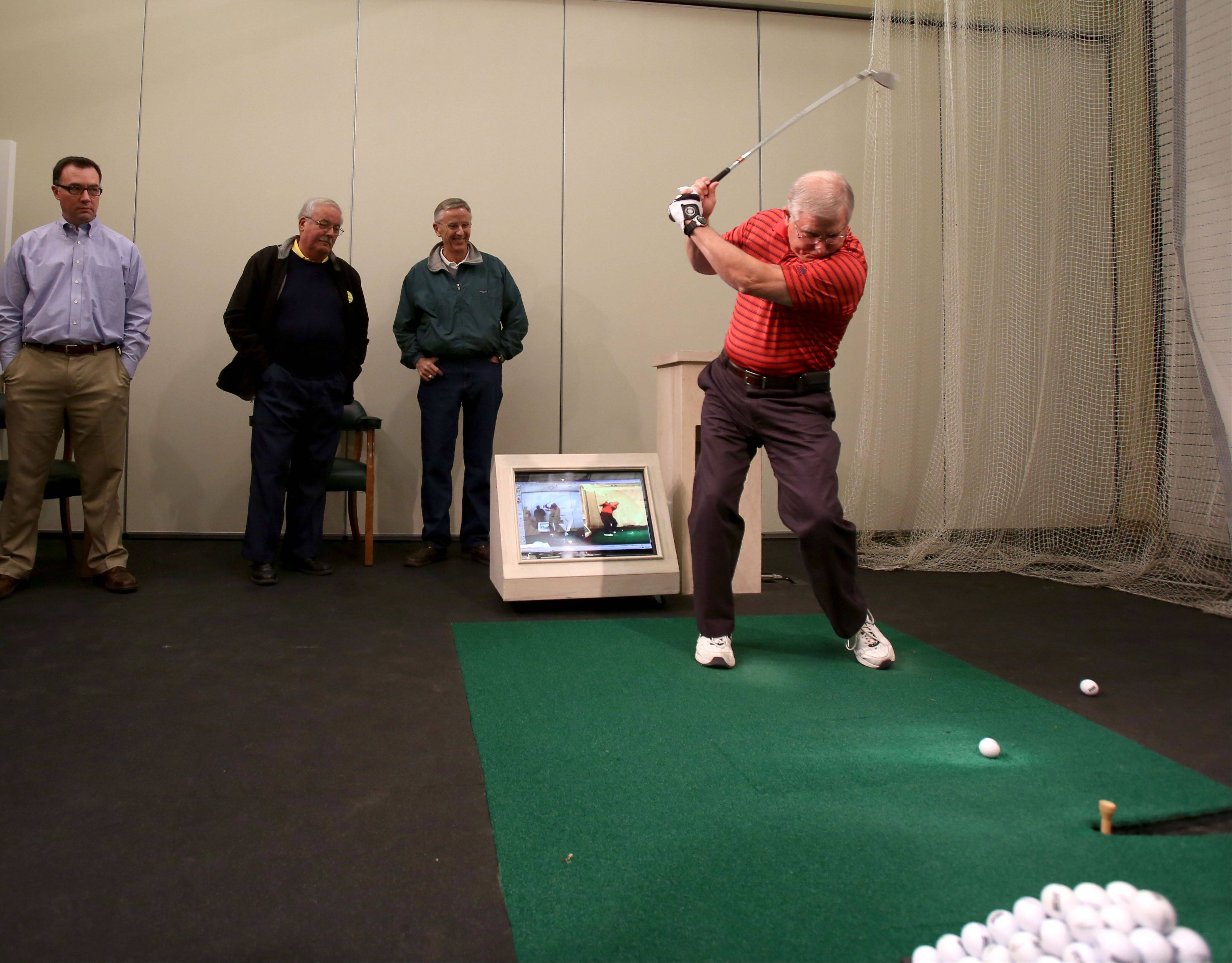 Gregory Collins of Antioch tries out his golf swing during the Daily Herald Subscriber Total Access event Monday at the Cantigny Golf Academy at Cantigny Park in Wheaton. Collins and other guests were able to try out their golf swings in the swing analysis room at the academy.