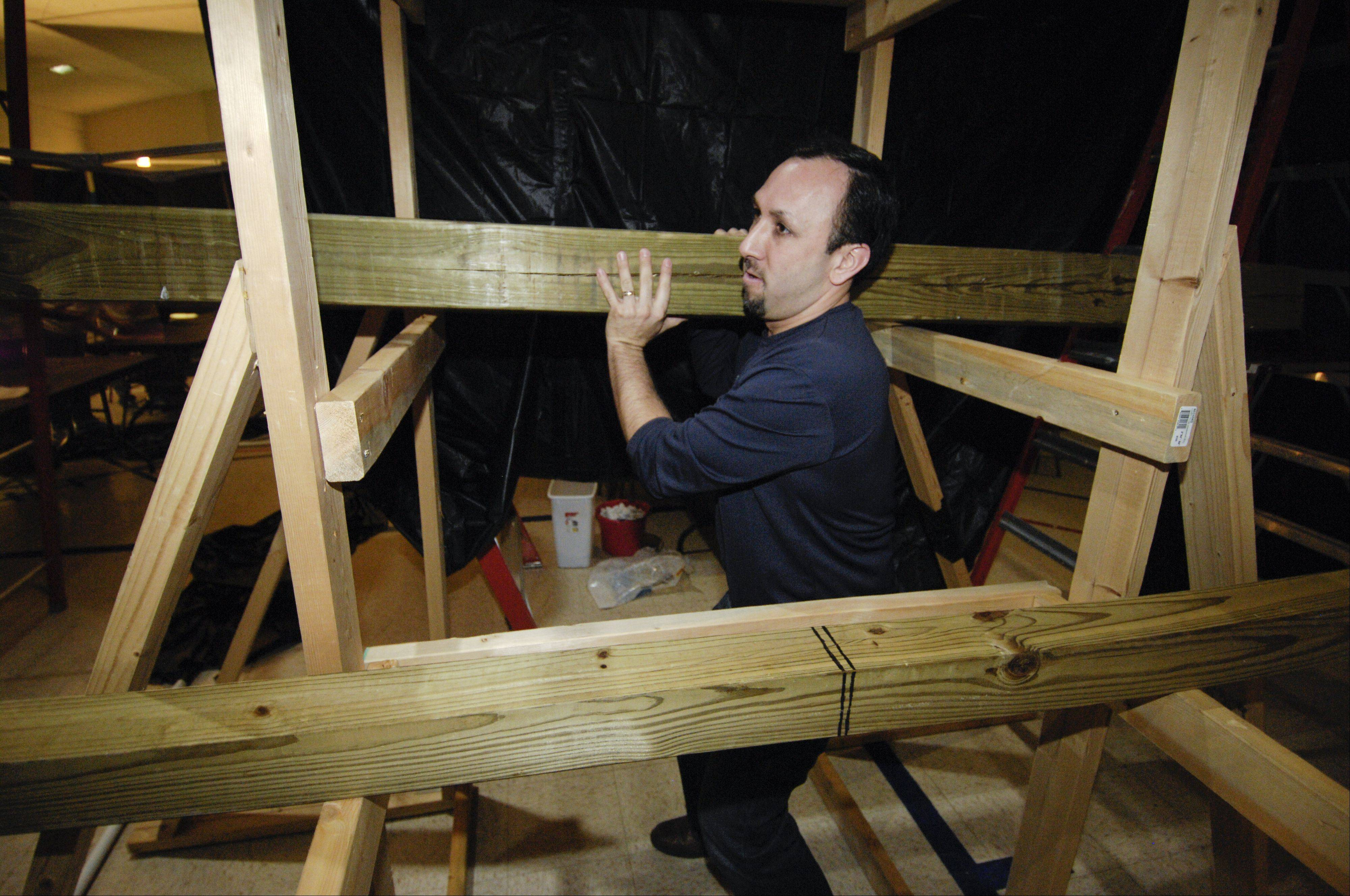 The Rev. Kevin Gushiken demonstrates lifting a large wooden beam that simulates the cross that Jesus carried. Harvard Avenue Evangelical Free Church in Villa Park is sponsoring an Easter Maze that will lead people through the events leading to the crucifixion.