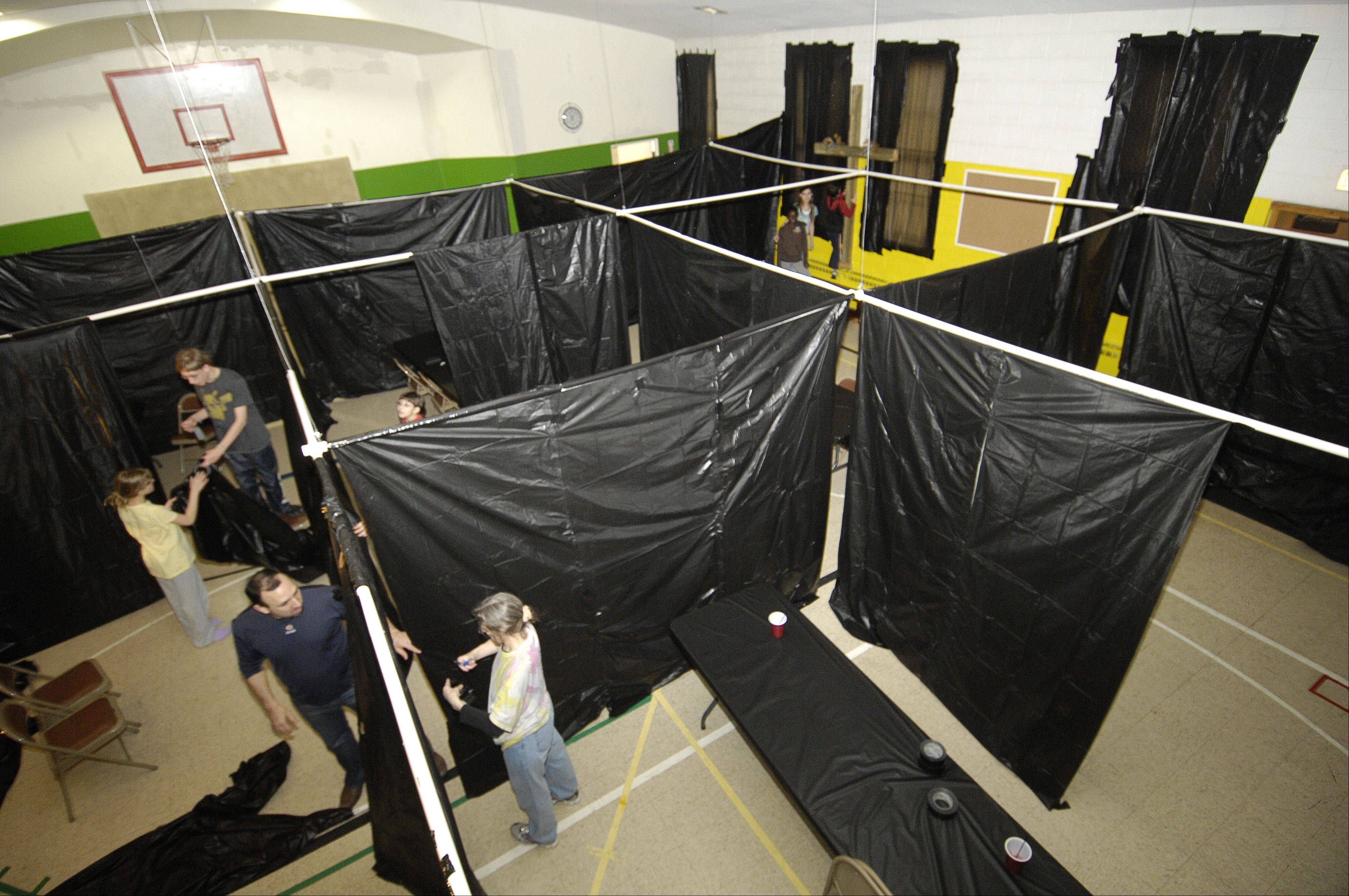 Congregation members at Harvard Avenue Evangelical Free Church in Villa Park set up temporary walls that will create an Easter Maze that opens Tuesday.