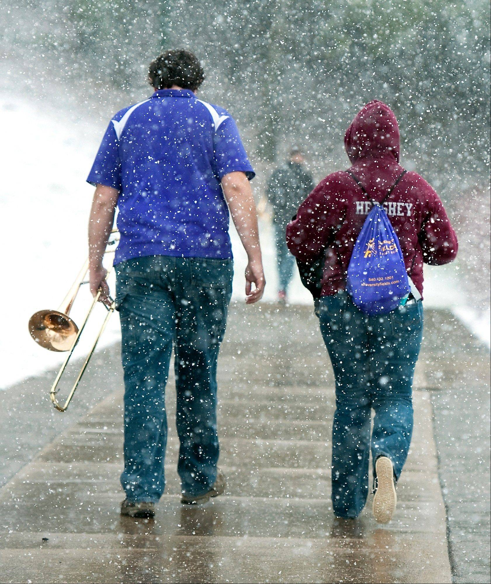 Junior Aaron Raffeinner, 20, left, and Holly Doherty, 19, a sophomore, members of the James Madison University Pep Band, leave the Convocation Center as the snow falls after performing during the second round Women's National Invitational Tournament basketball game with North Carolina State Sunday March 24, 2013 in Harrisonburg, Va.