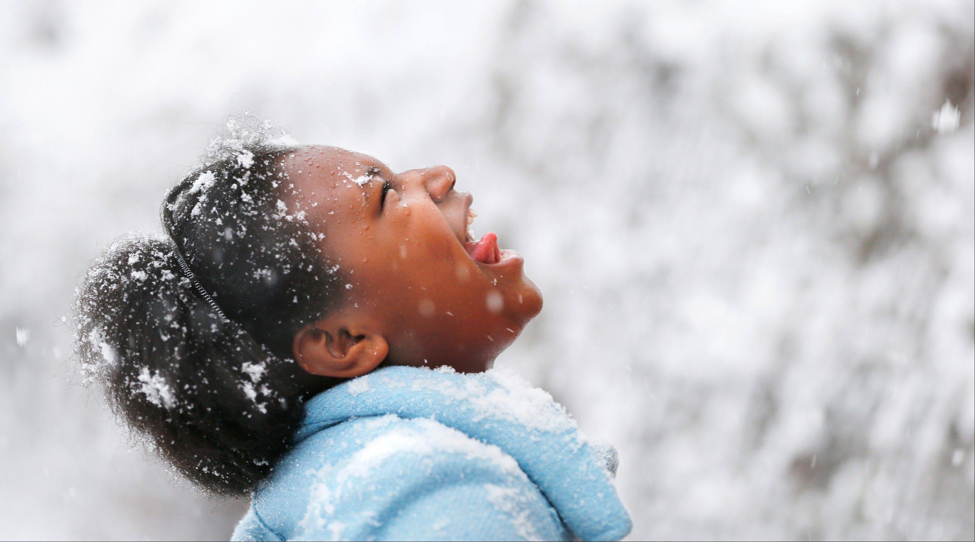 Destiny Chew, age 11, tries to catch snowflakes on her tongue as she stands along Q Street in Richmond, Va. Sunday, March 24, 2013.