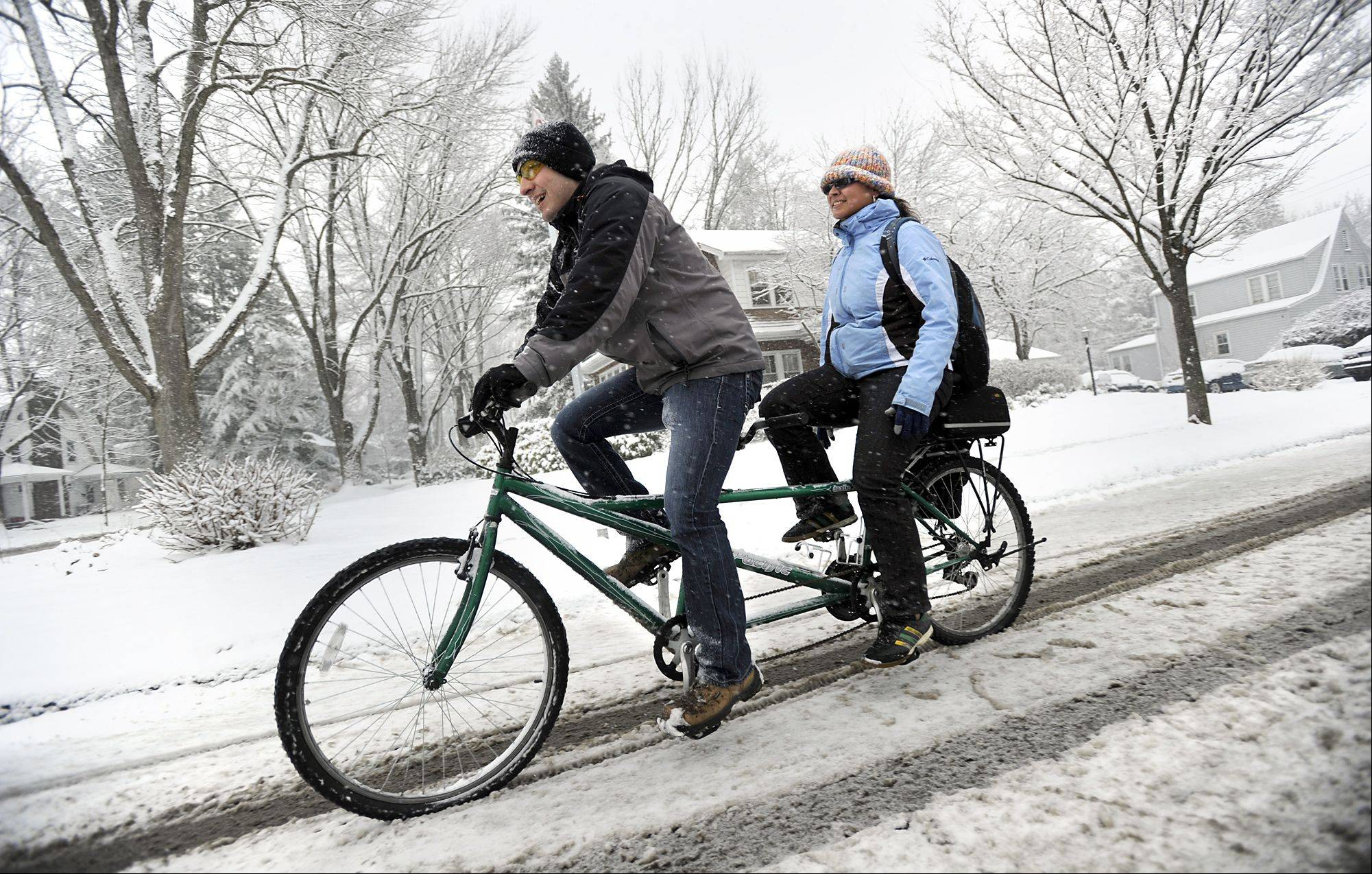 Penn State students David Leinbach and Samantha Rosado ride a tandem bicycle to campus along N Allen Street, in State College, Pa., Monday, March 25, 2013. Heavy snow fell throughout Centre County, Monday, causing local schools to be closed and hazardous traveling conditions.