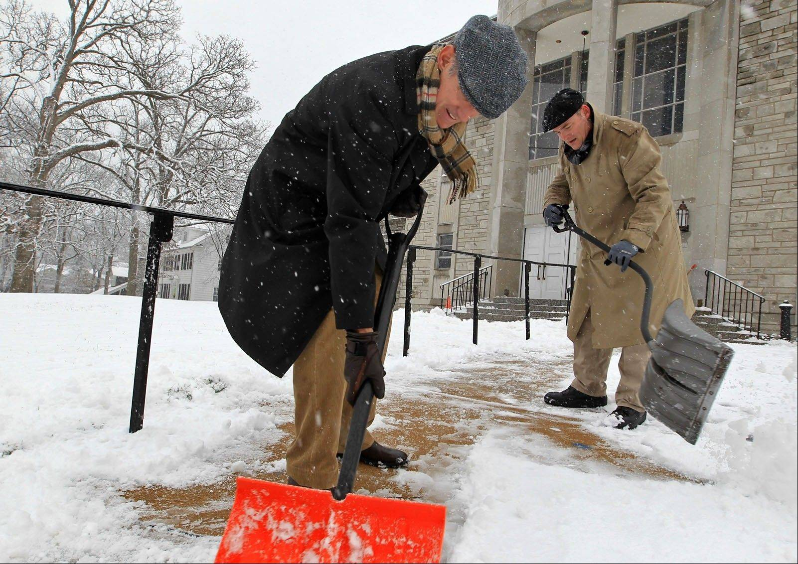 Volunteers Tim Noonan and Larry Voss, both of Glendale, Mo., shovel the walks in front of Mary Queen of Peace Church in nearby Webster Groves, Mo., on Sunday morning, March 24, 2013, before going inside for Mass.