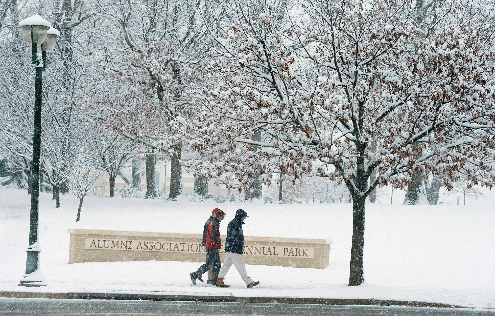 James Madison University students walk along Carrier Drive at the Alumni Association Centennial Park during the snow in Harrisonburg, Va., Sunday evening March 24, 2013.