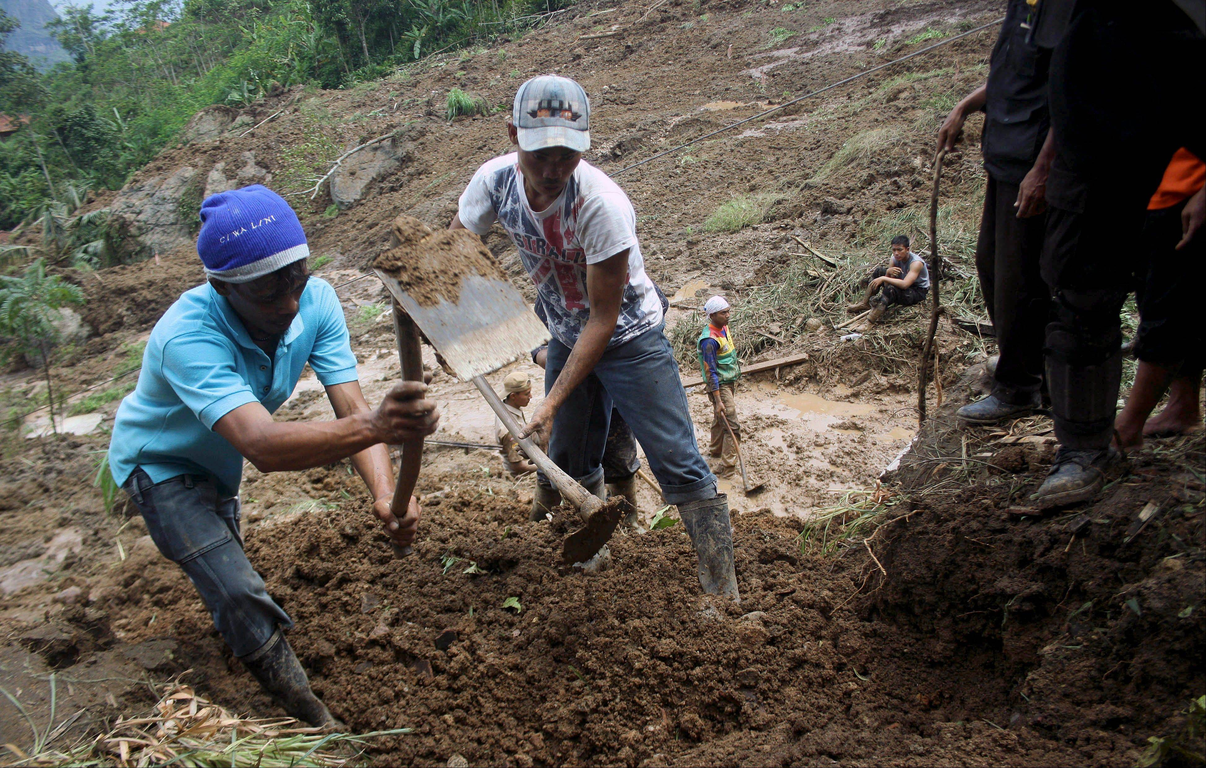 Villagers use hoes as they search for victims of a landslide that hit a village in Cililin, West Java, Indonesia, Monday.