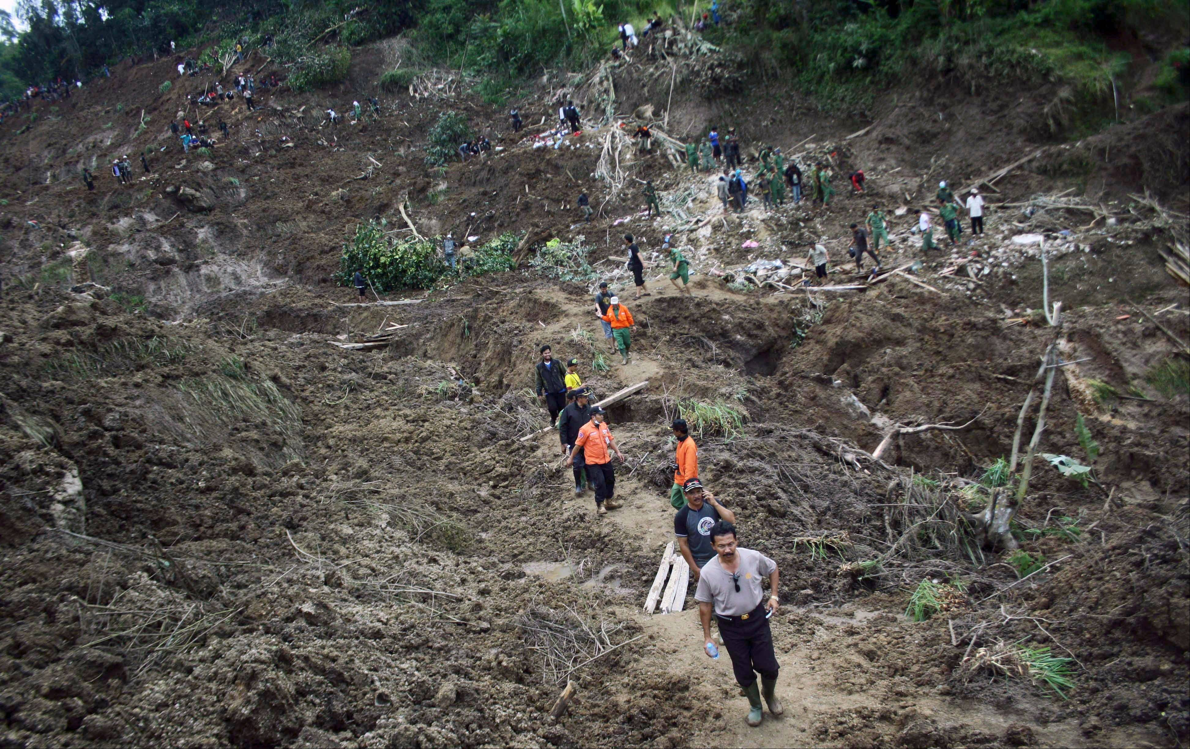 Rescuers search for victims at a village that was hit by a landslide in Cililin, West Java, Indonesia, Monday.