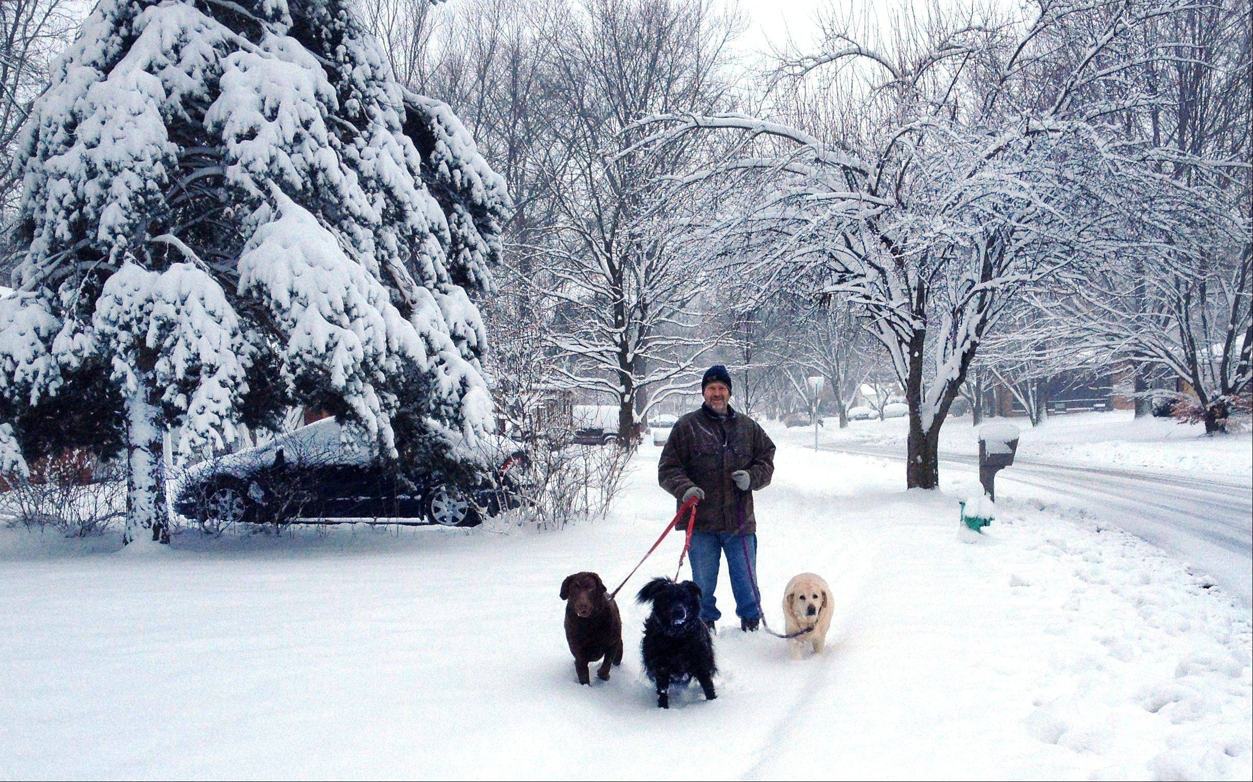 Dennis Catron walks his three dogs along Darby Lane through the Greenbriar neighborhood on Indianapolis' far Northside on Monday, March 25, 2013 after more than seven inches of snow fell overnight.
