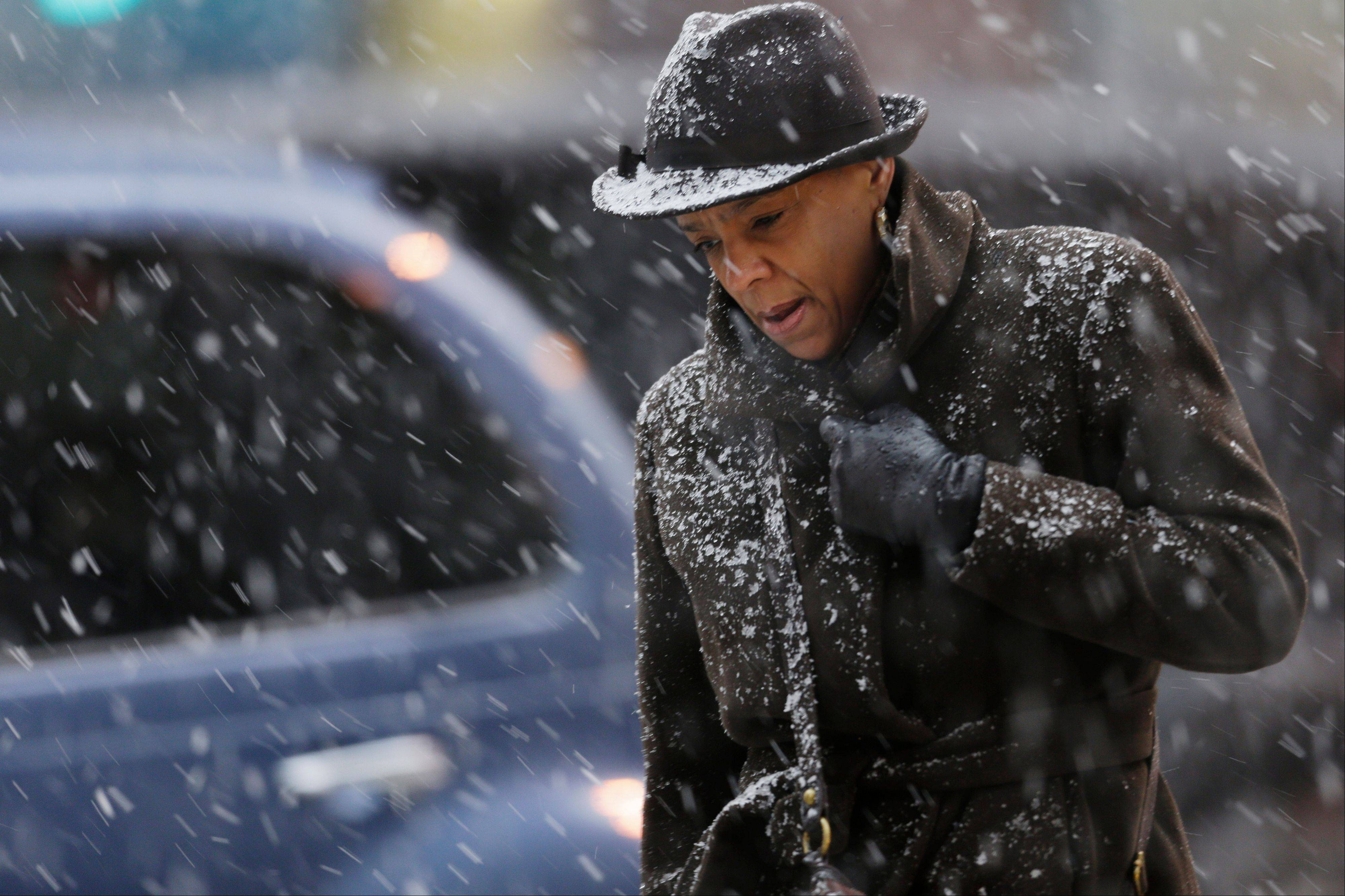 A commuter walks through a spring snowstorm Monday, March 25, 2013, in Philadelphia. The storm that blanketed the Midwest with heavy snow and slush continues its push east.