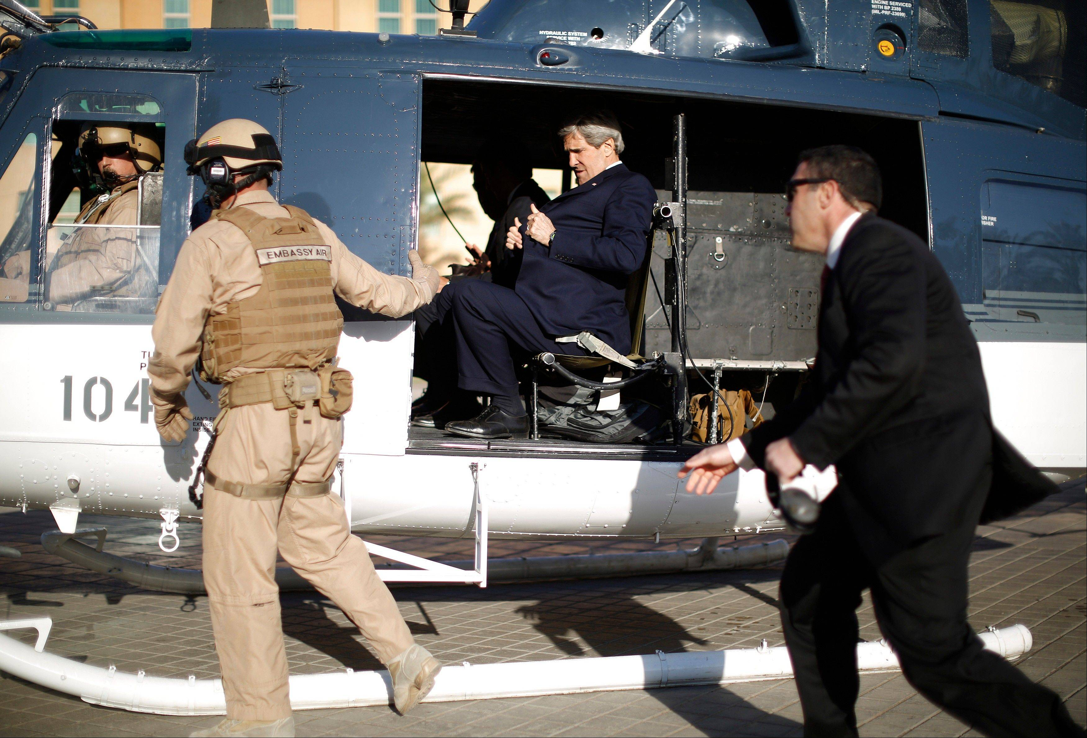 U.S. Secretary of State John Kerry straps himself into a helicopter as he prepares to fly out of the U.S. Embassy in Baghdad Sunday. Kerry went to Afghanistan Monday on an unannounced visit to meet with Afghan President Hamid Karzai.